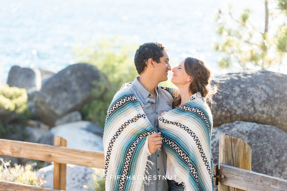 couple eskimo kissing while cuddling in a blanket for their summer Tahoe engagement