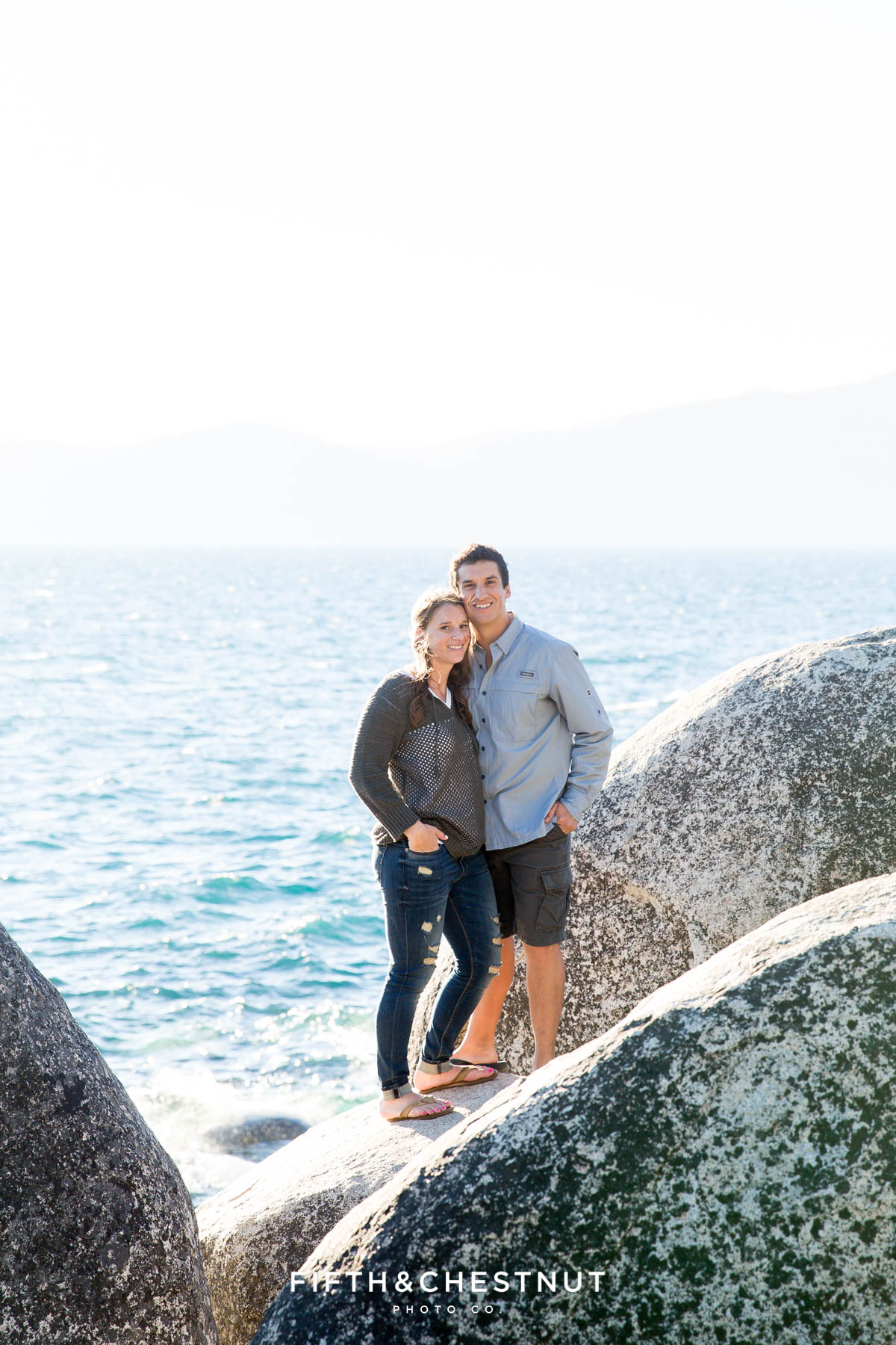 couple stands on rocks overlooking Lake Tahoe