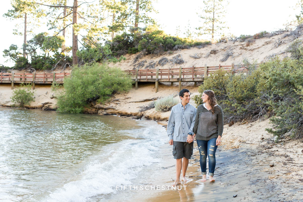 couple walks down the beach of sand harbor hand in hand