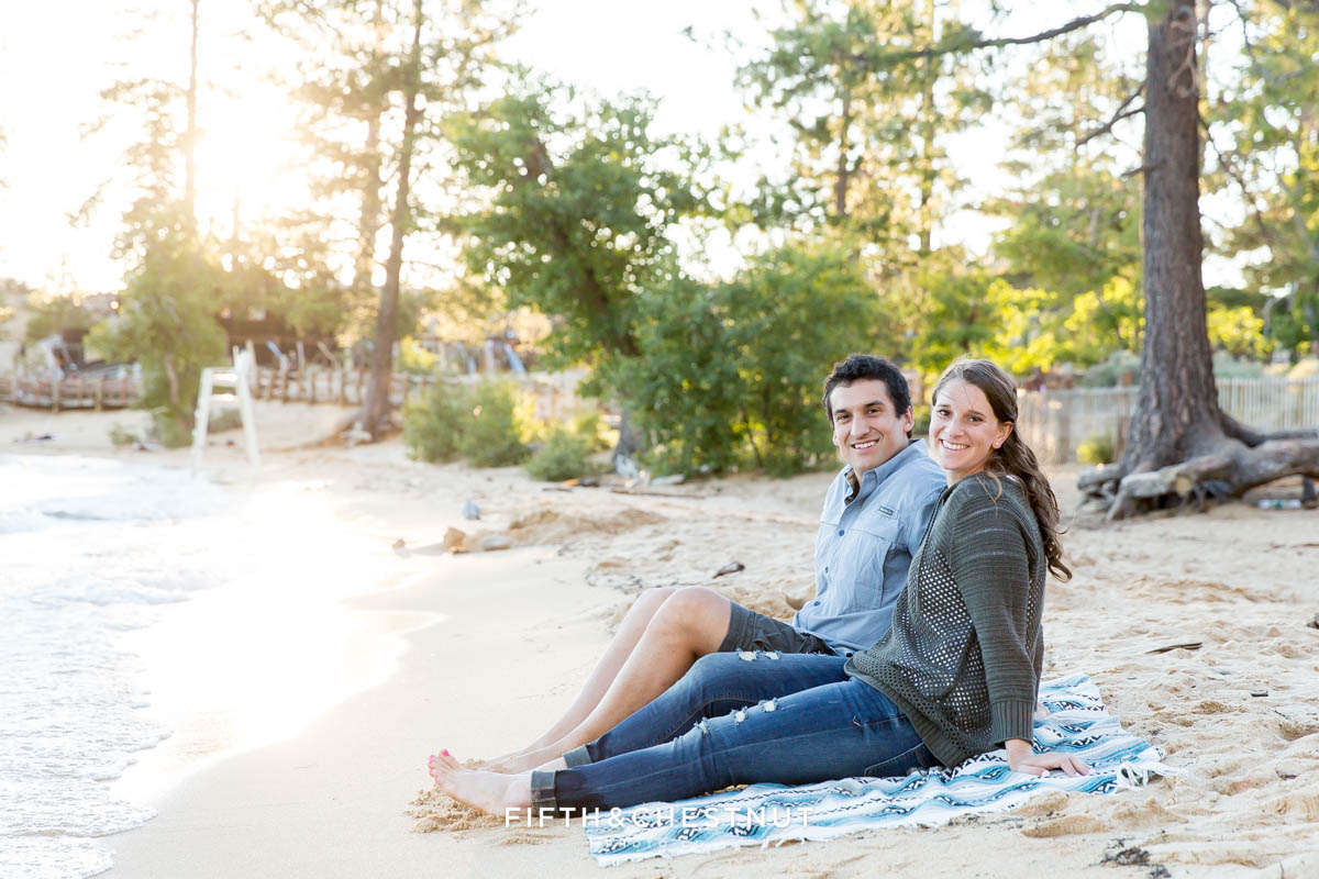 couple sits on the sandy shore of Lake Tahoe for their summer Tahoe engagement