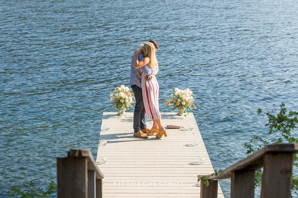 Newly engaged couple hug on the end of a romantic dock on Donner Lake after their marriage proposal