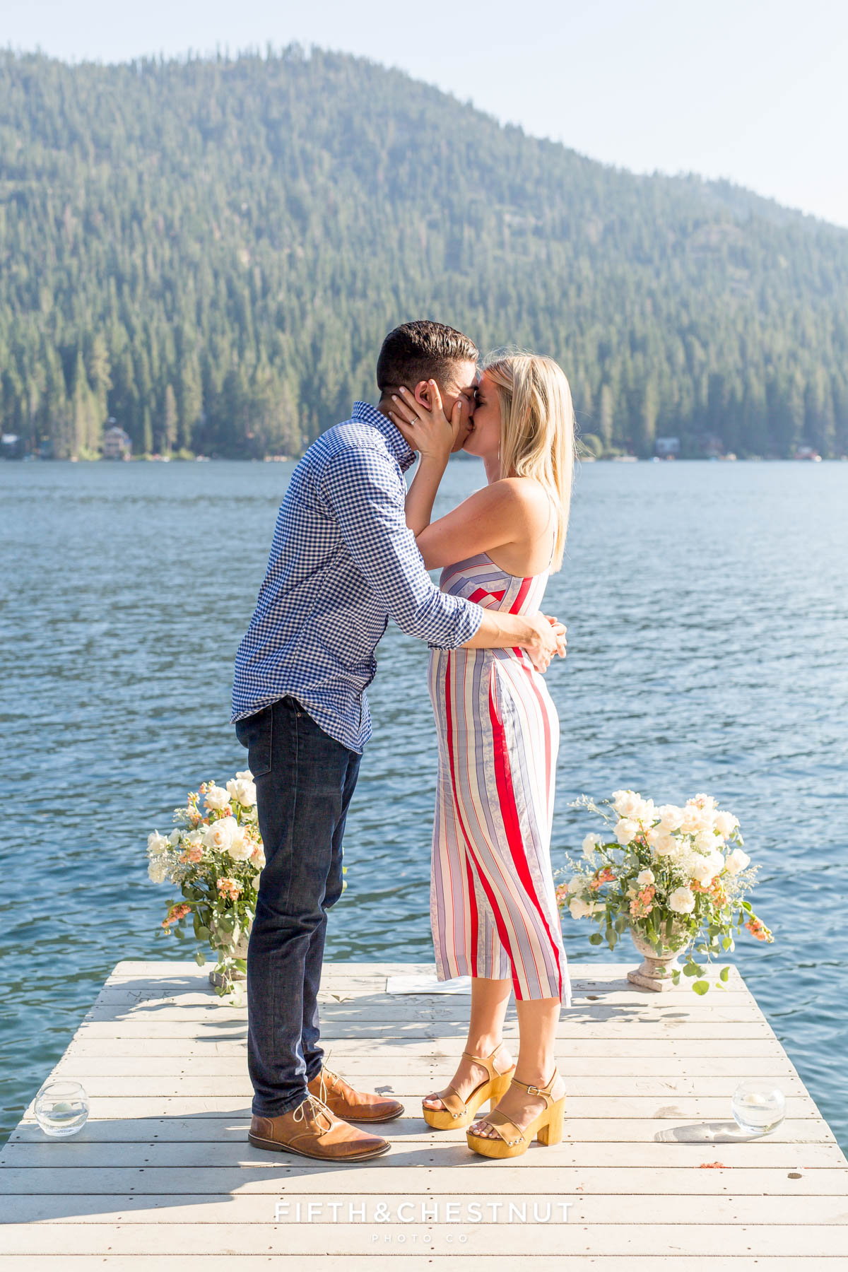 Newly engaged couple kissed with Donner Lake and trees in the background after their Donner Lake Proposal