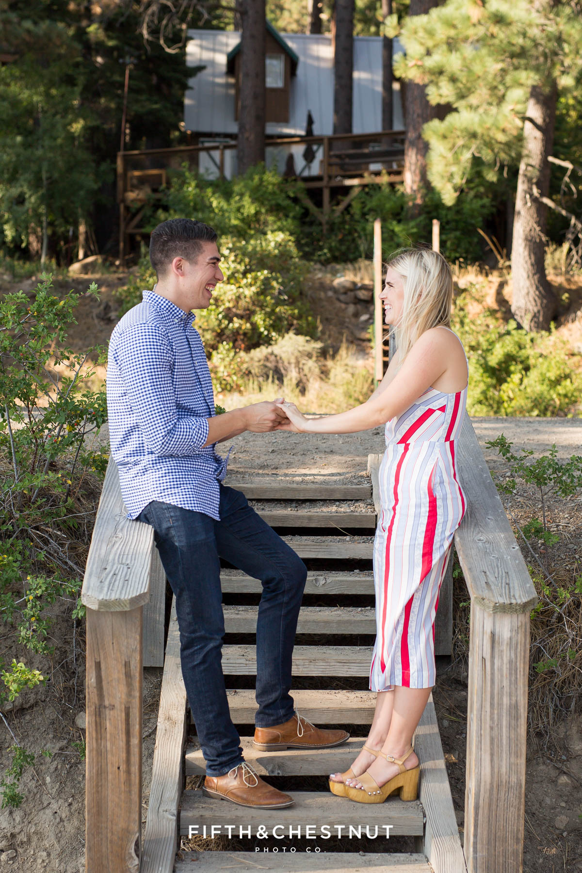 Newly engaged couple holds hands on steps leading to a private dock in Donner Lake after their Donner Lake Proposal