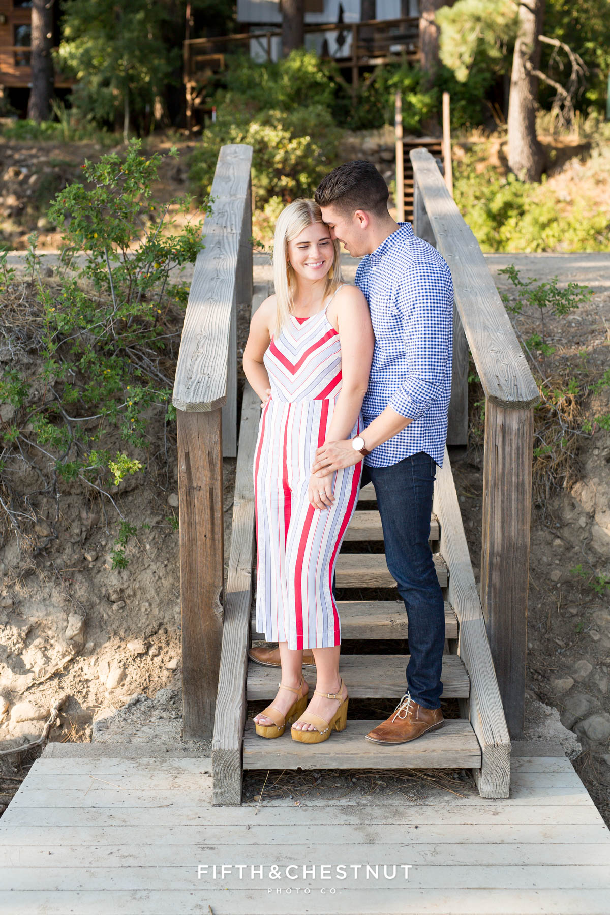 Groom-to-be whispers in his fiance's ear on steps of a dock after their romantic Donner Lake Proposal
