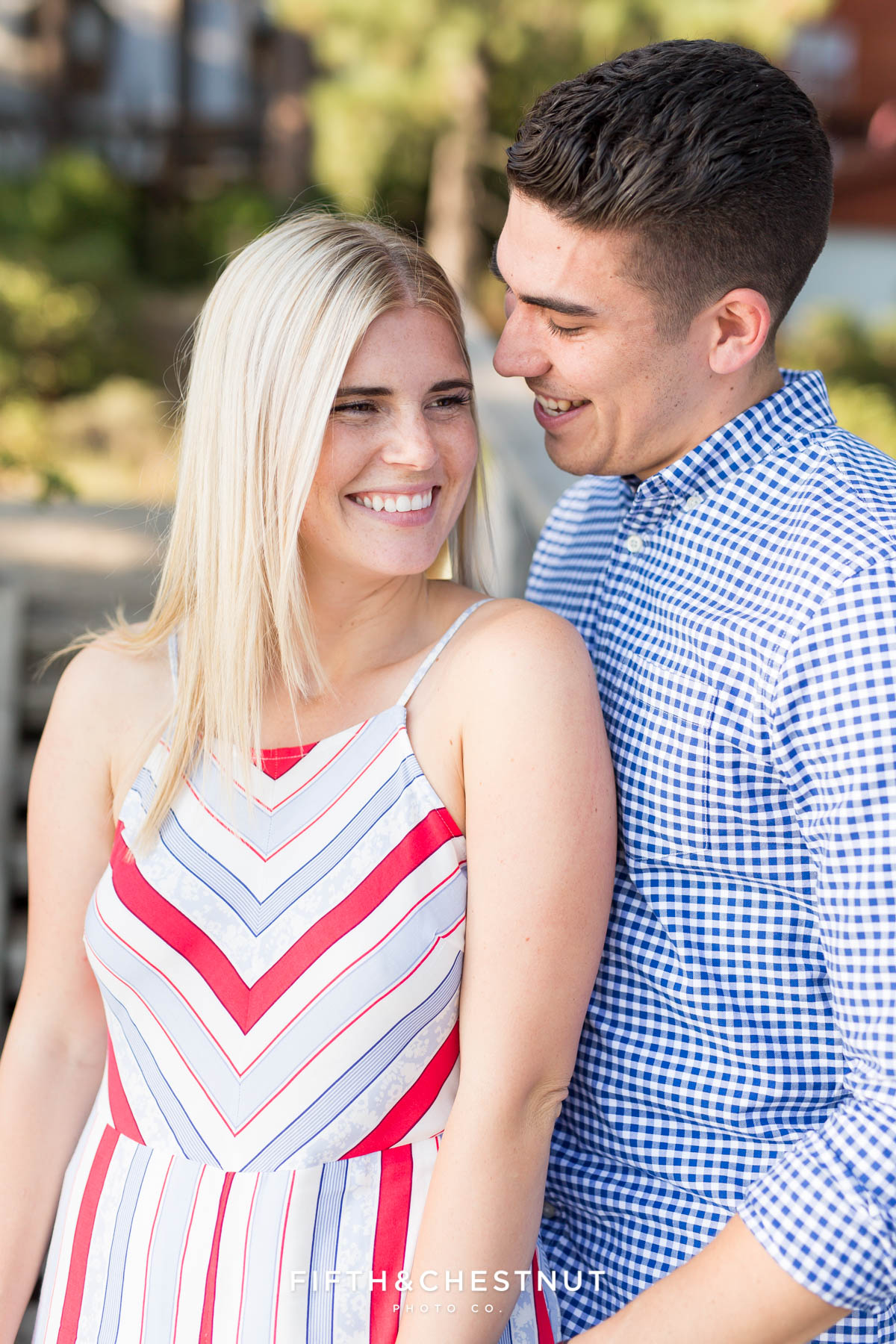 After their Donner Lake Proposal, newly engaged couple smiles and laughs together as they celebrate