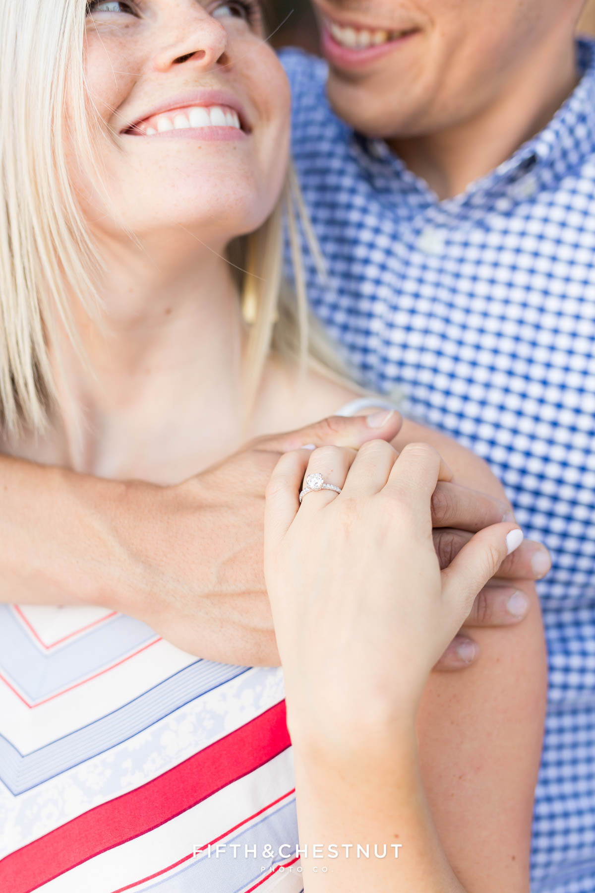 bride-to-be looks up to her groom as she shows off her gorgeous engagement ring
