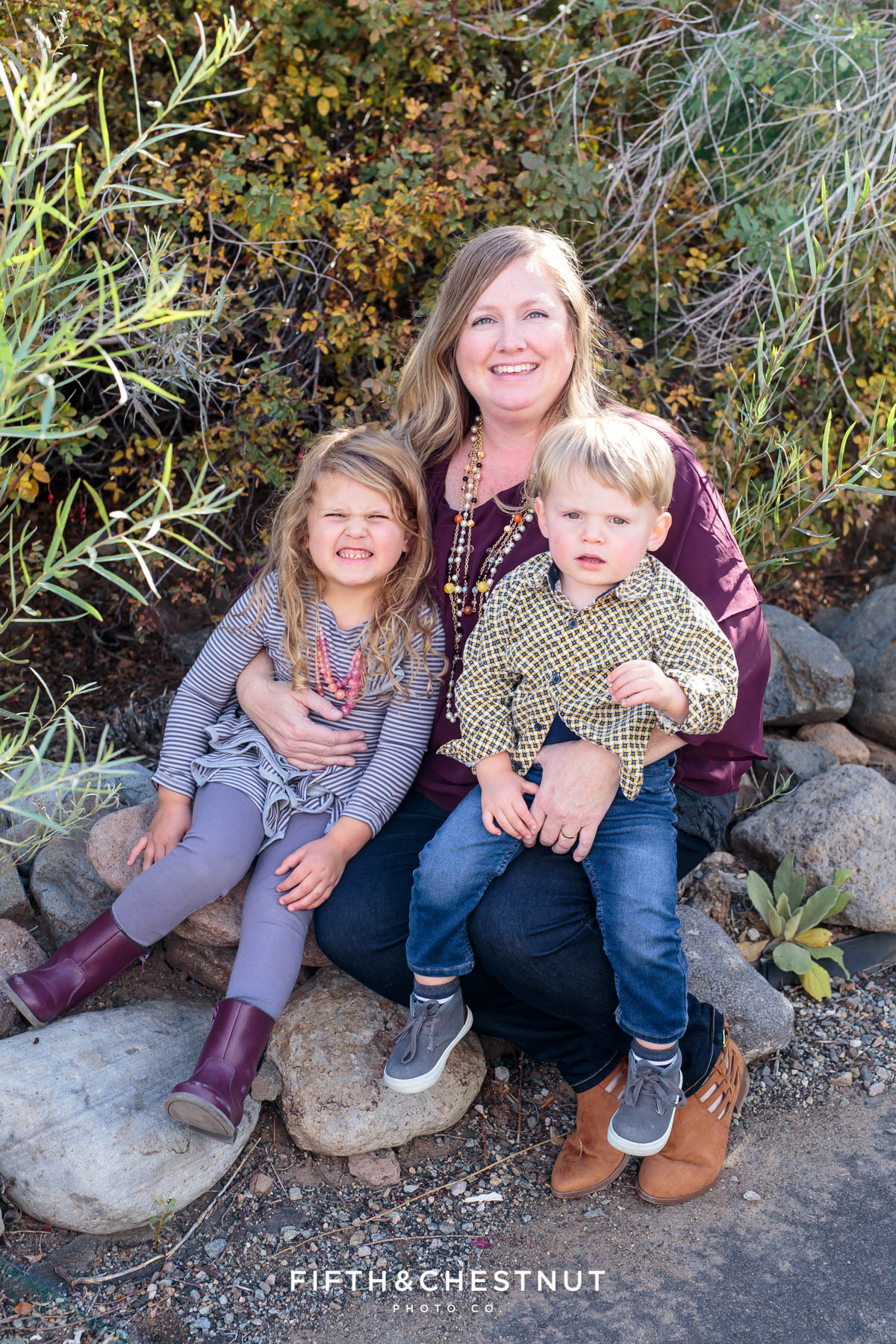 mom and two kids sit on rocks for Bartley Ranch Portraits by Reno Family Photographer