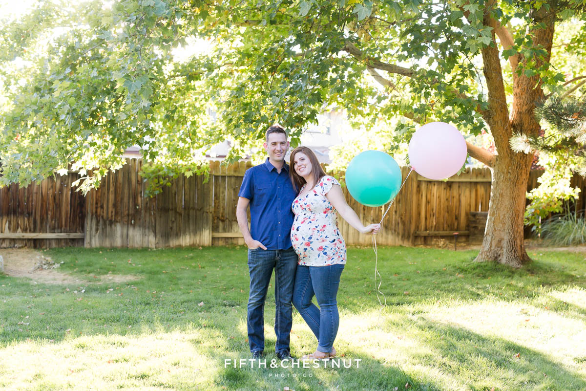 Twin gender reaveal with couple holding a blue balloon and a pink balloon