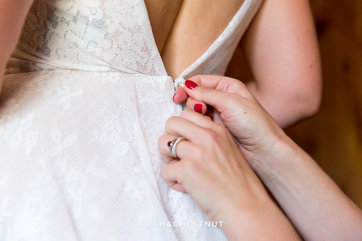 bride's dress getting zipped up for her bohemian Greenhorn Creek Guest Ranch Wedding