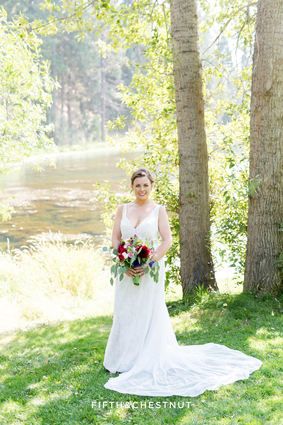 bride in front of a pond for her bright and summery wedding bouquet for a Greenhorn Creek Guest Ranch Wedding