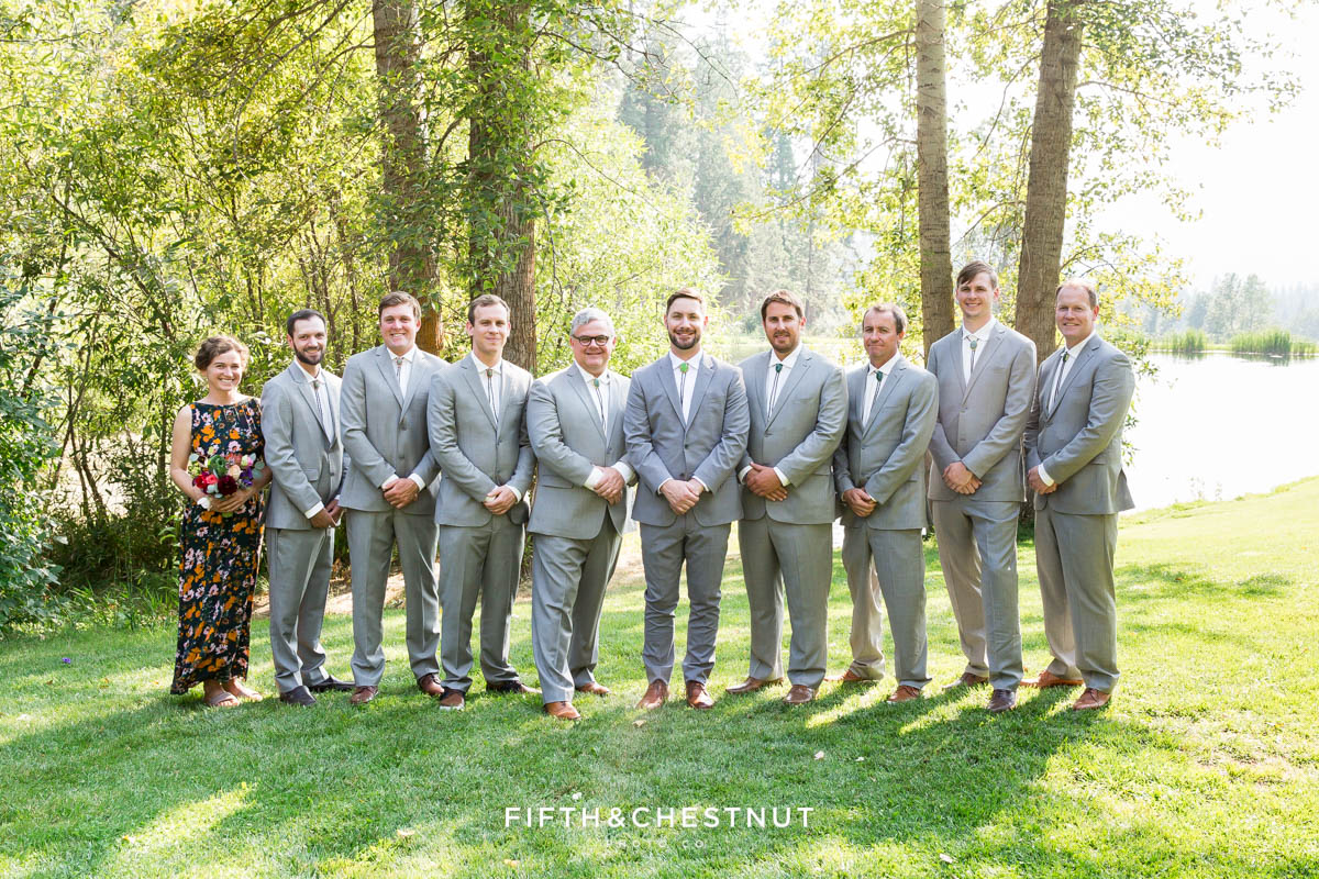 groomsmen in gray and a groomswoman in floral dress for a wedding party in gray suits and floral dresses for a bright and summery wedding bouquet for a Greenhorn Creek Guest Ranch Wedding