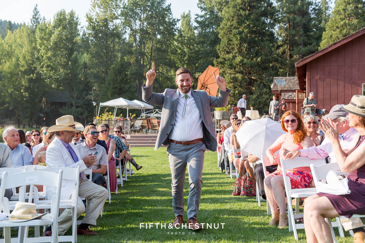 groom excitedly walks down the aisle before his Greenhorn Creek Guest Ranch Wedding ceremony