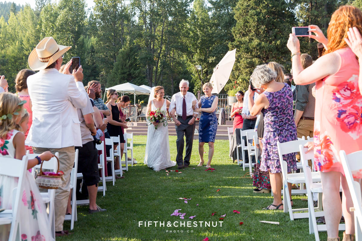 bride walks down the aisle with her father and mother for a Greenhorn Creek Guest Ranch Wedding