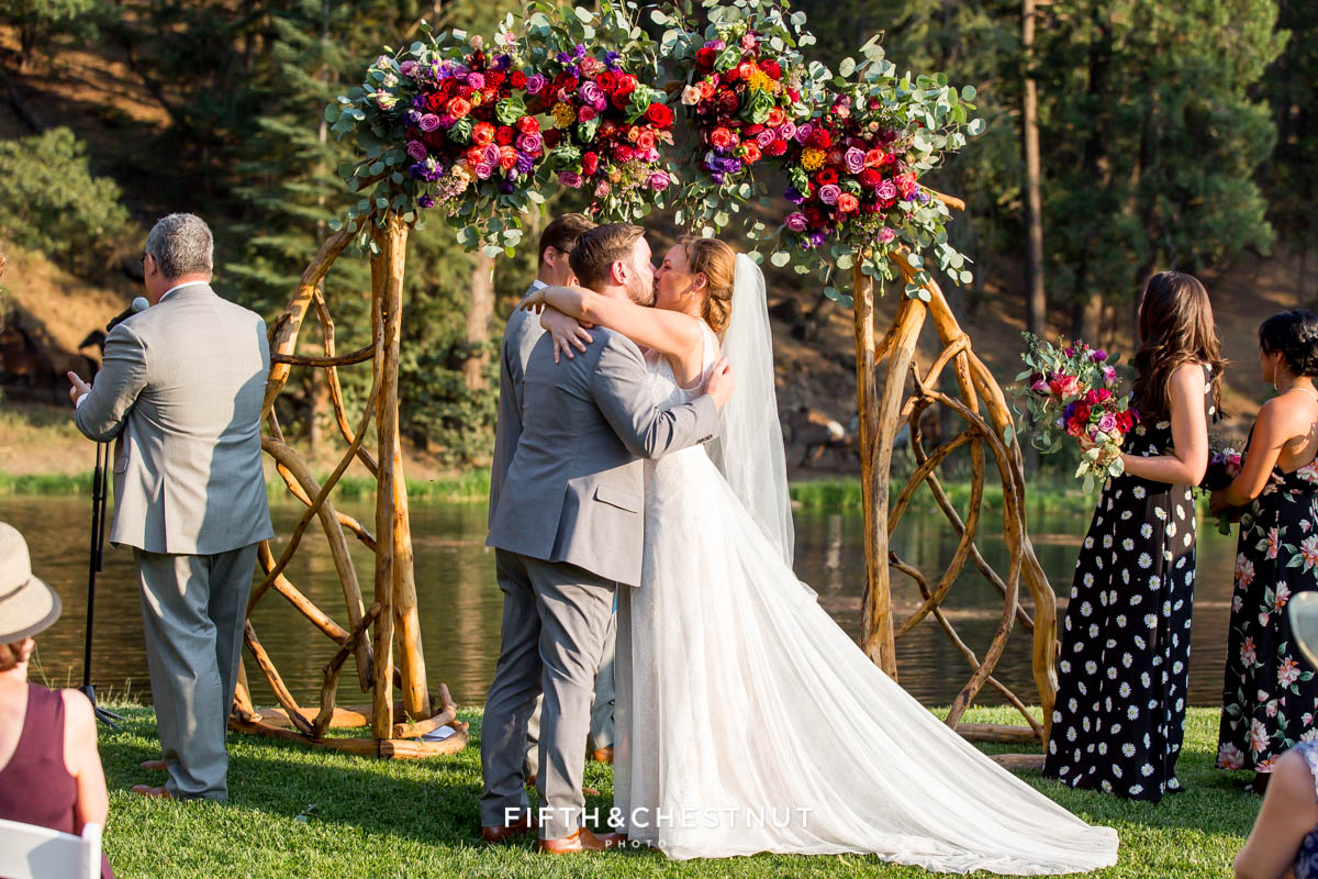 bride and groom kiss while horses rum wildly behind their ceremony site at their Greenhorn Creek Guest Ranch Wedding