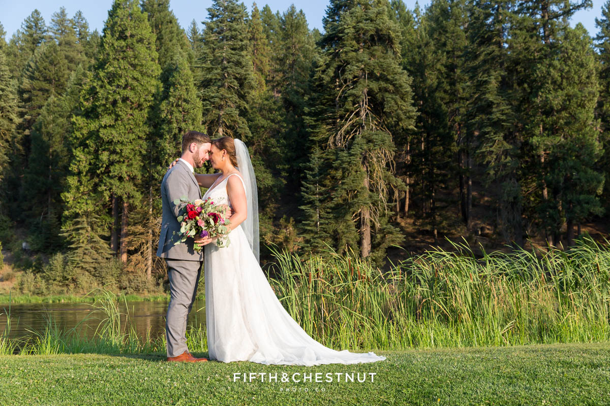 bride and groom place their foreheads together for a portrait in front of the lovely pond at their Greenhorn Creek Guest Ranch Wedding