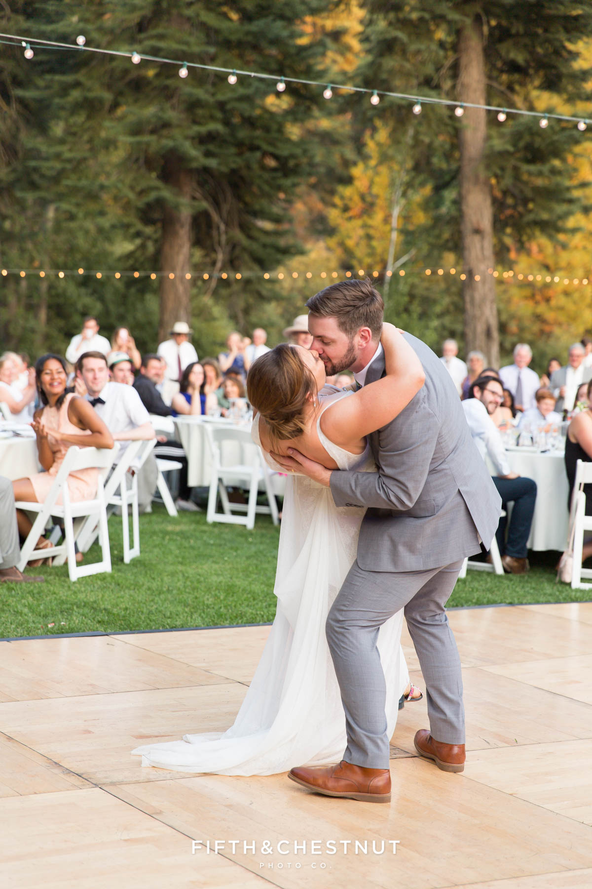 groom lowers bride on the dance floor for a kiss before their first song is over as hubsband and wife