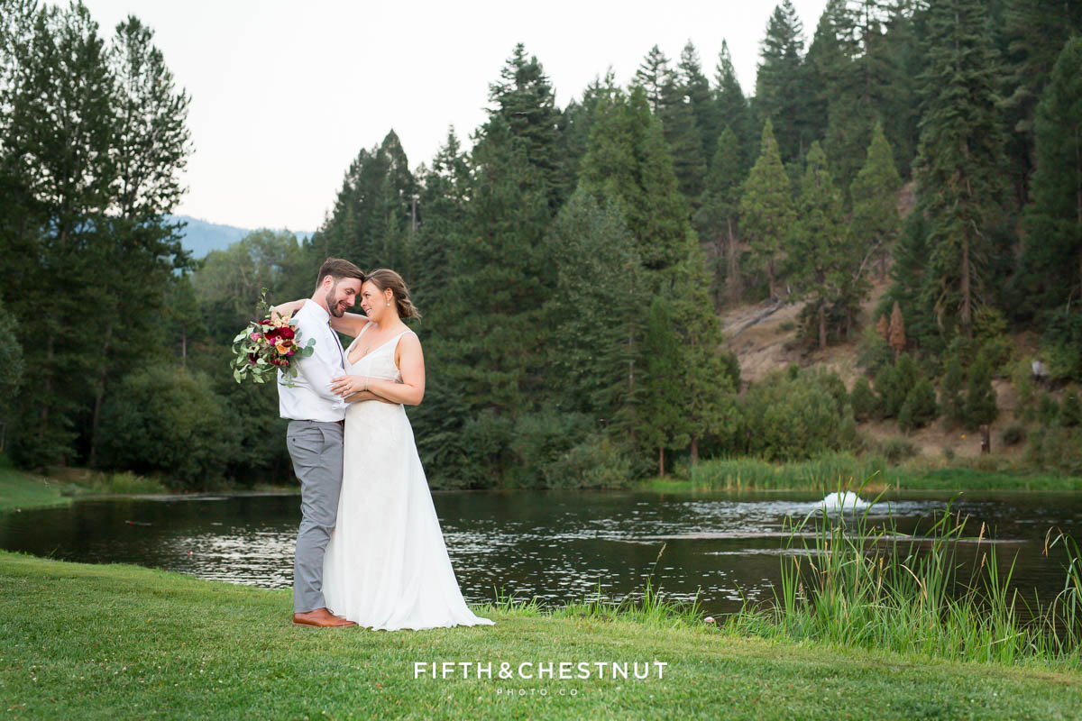 bride and groom pose for romantic portraits in front of the pond during their Greenhorn Creek Guest Ranch Wedding reception