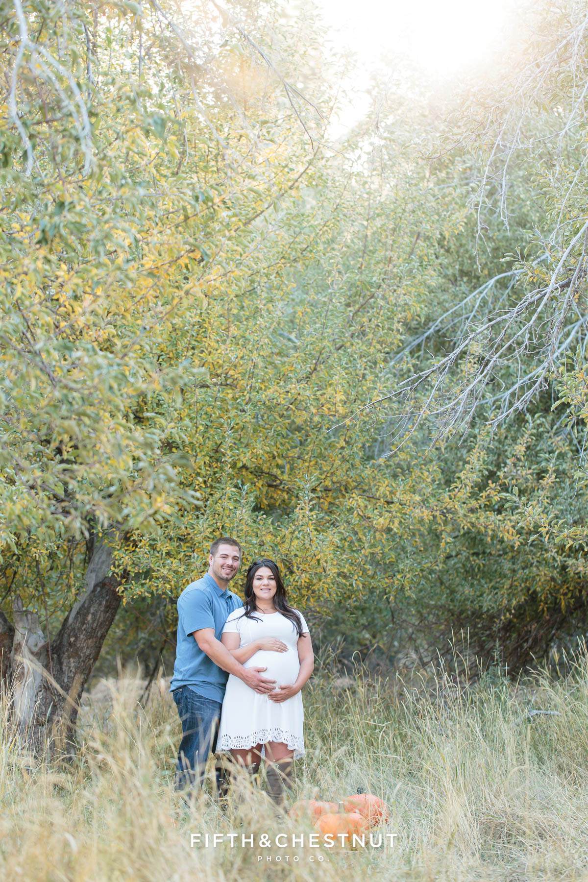 Husband and expecting wife stand in apple orchard with pumpkins for their fall maternity portraits