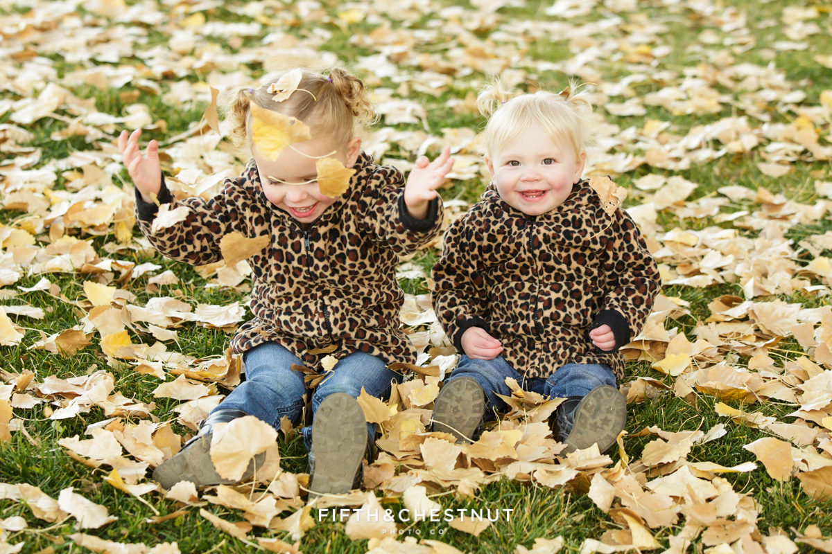 toddlers playing in fall leaves wearing cheetah print jackets for Mayberry Park Portraits