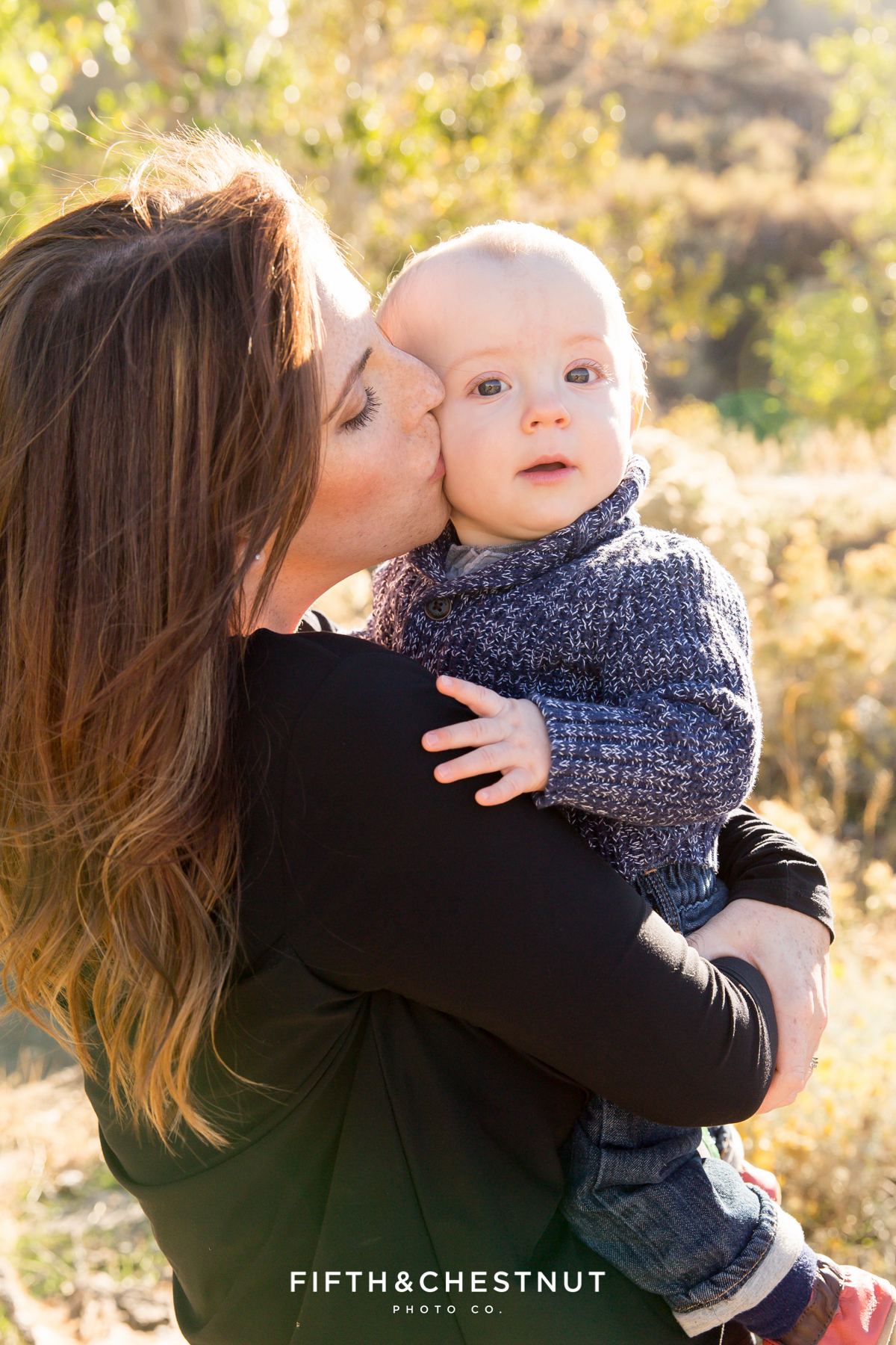 Mother kisses her baby's cheek for Mayberry Park Portraits in the fall