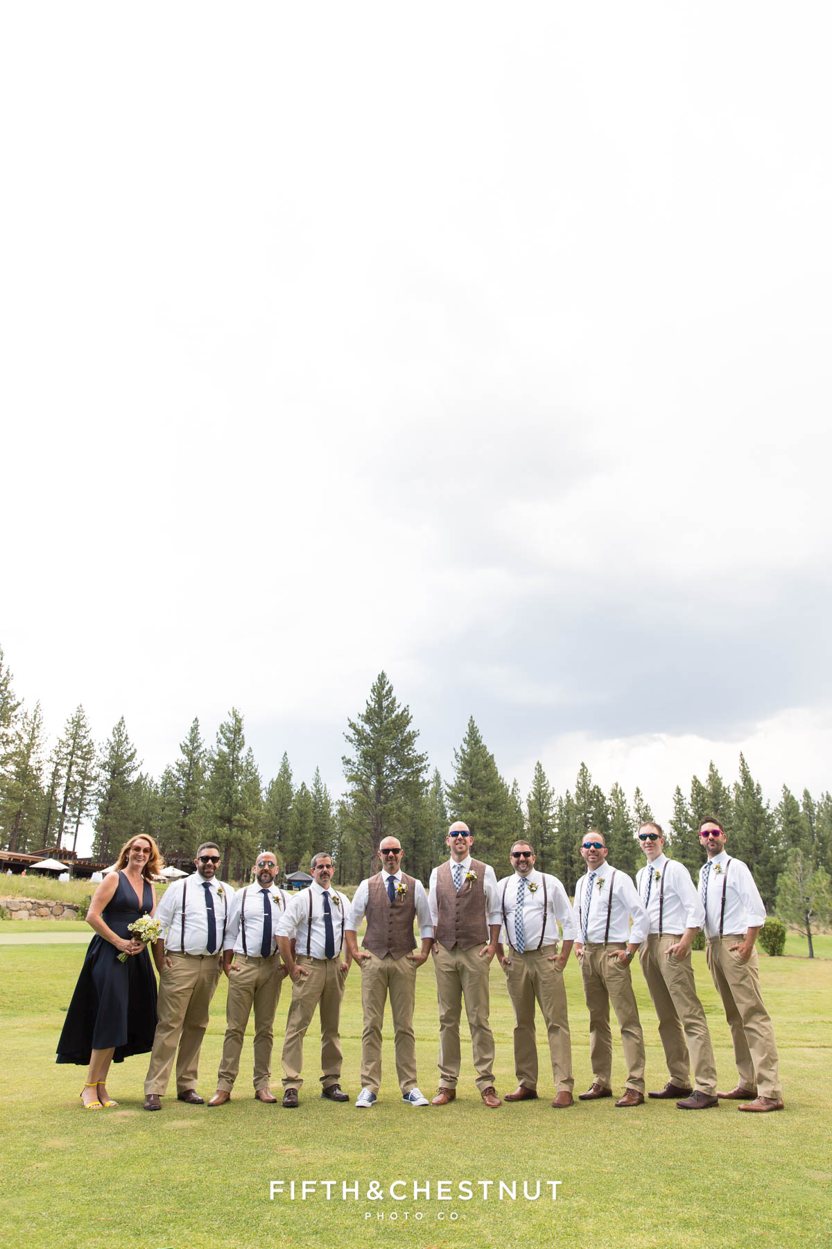 Wedding party stands in field with their sunglasses on before a gay wedding at PJ's at Gray's Crossing by Truckee Wedding Photographer
