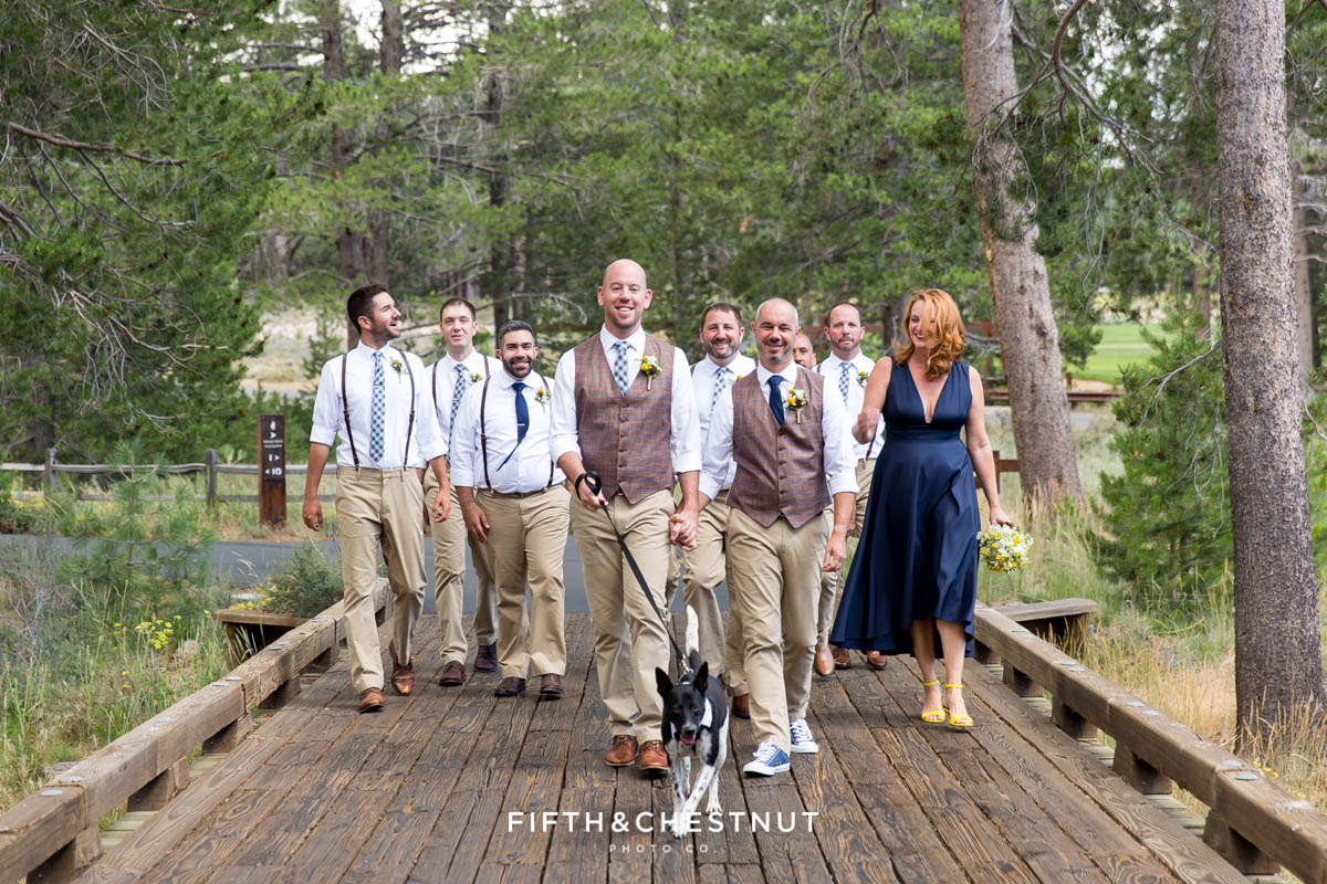 Grooms walk their dog, Cooper, down a wooden path in Truckee before their gay wedding at PJ's at Gray's Crossing