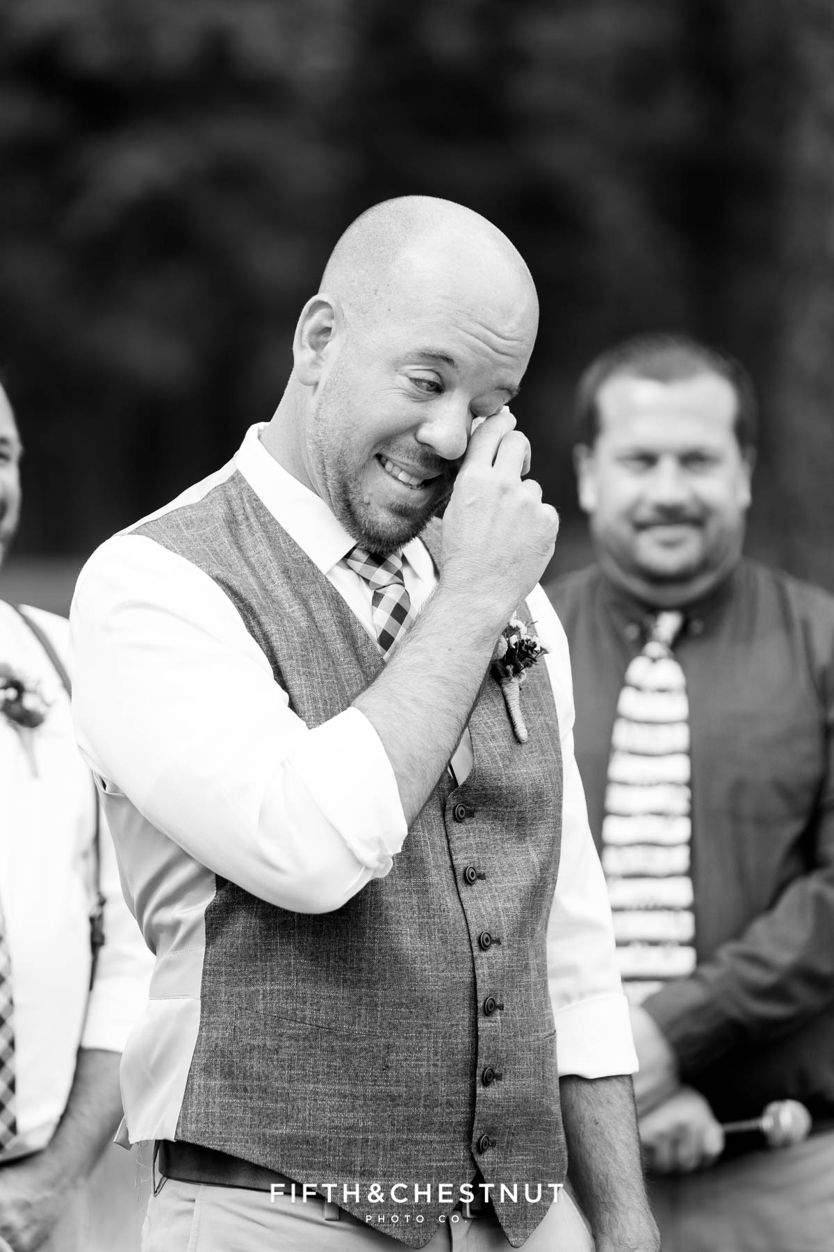 Black and white image of a groom wiping his tears during ceremony with officiant standing behind him looking on during his gay wedding at PJ's at Gray's Crossing in Truckee