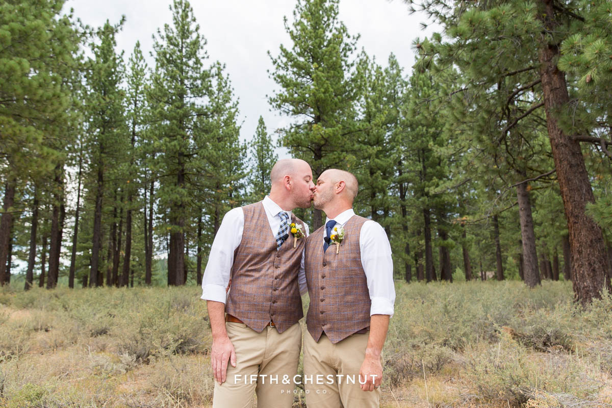 Grooms kiss in an open field after their Truckee Wedding at PJ's at Gray's Crossing