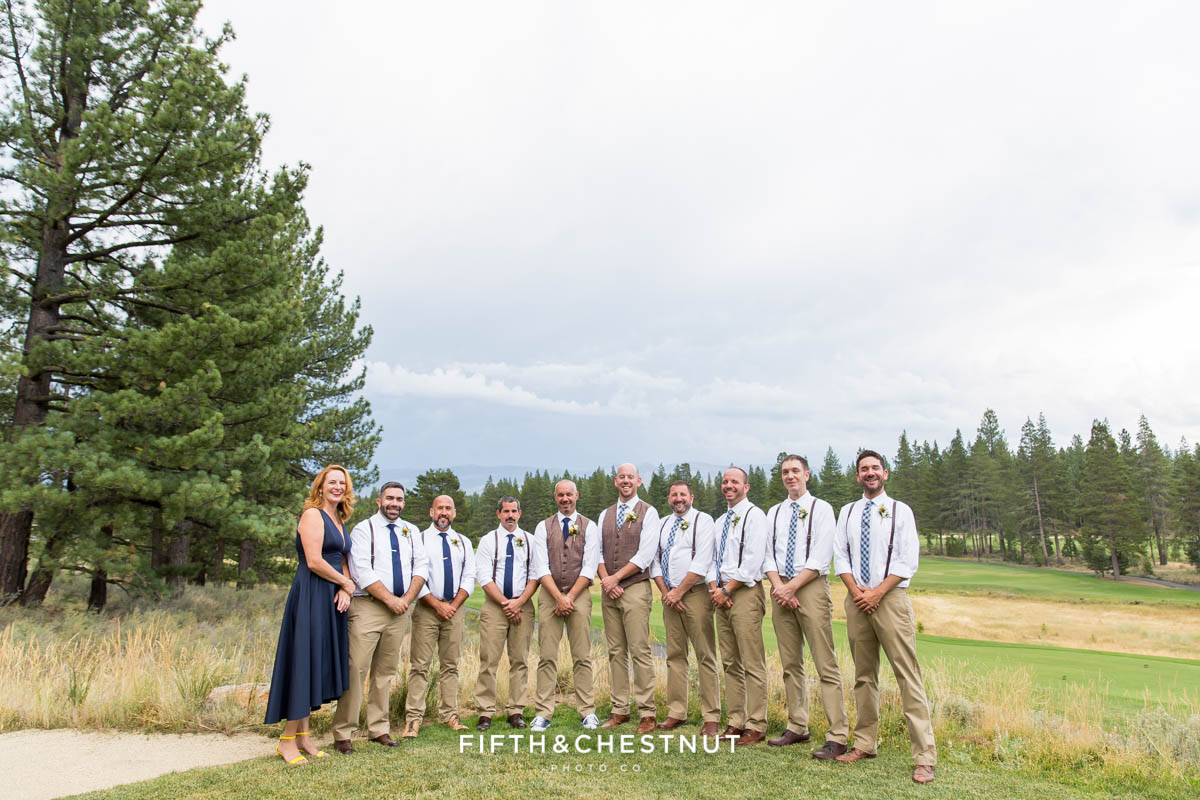 Wedding party stands together under stormy skies at a same-sex wedding in Truckee