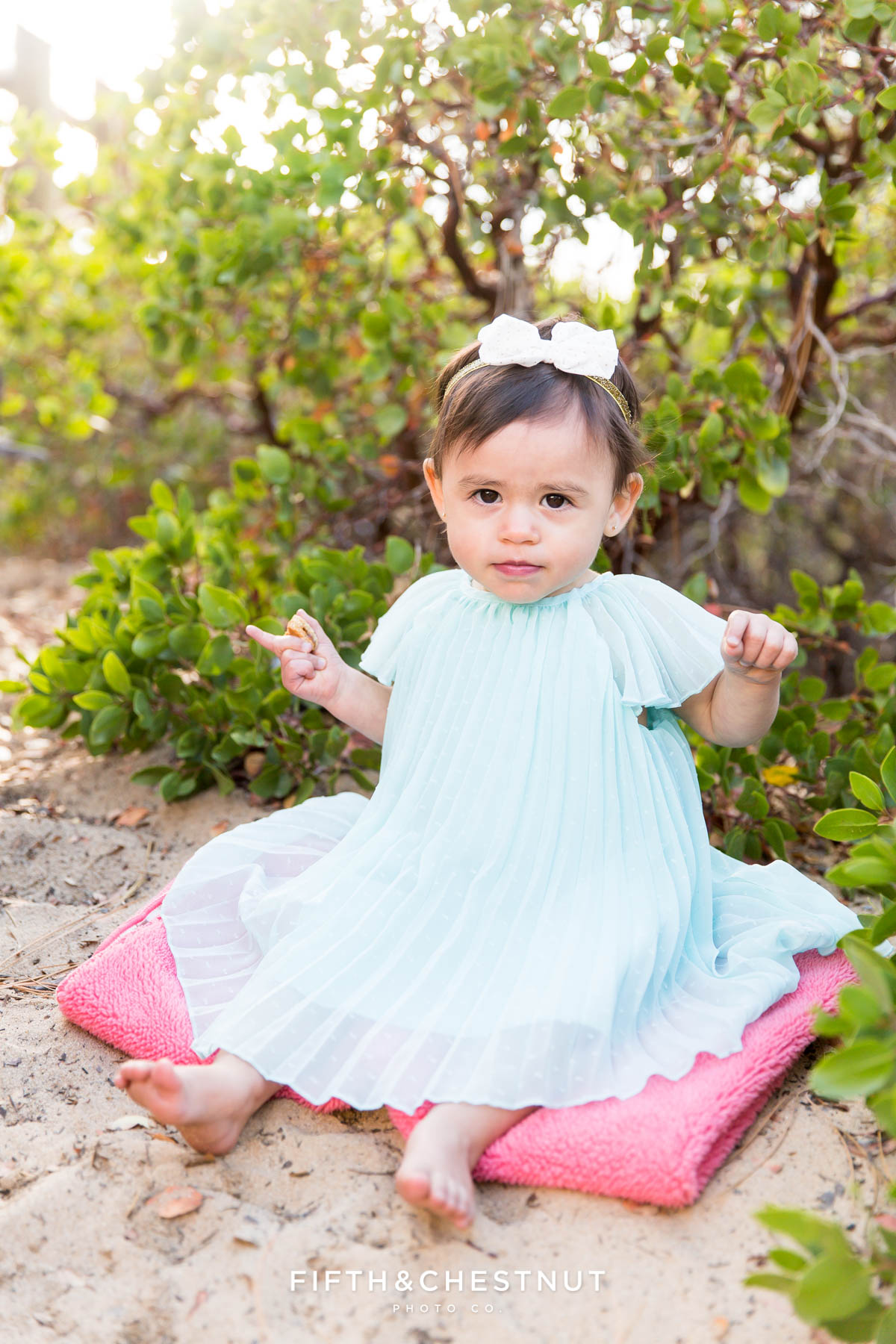one year old girl sits in sand wearing a mint green dress for her fashionable one year portraits by Reno child photographer