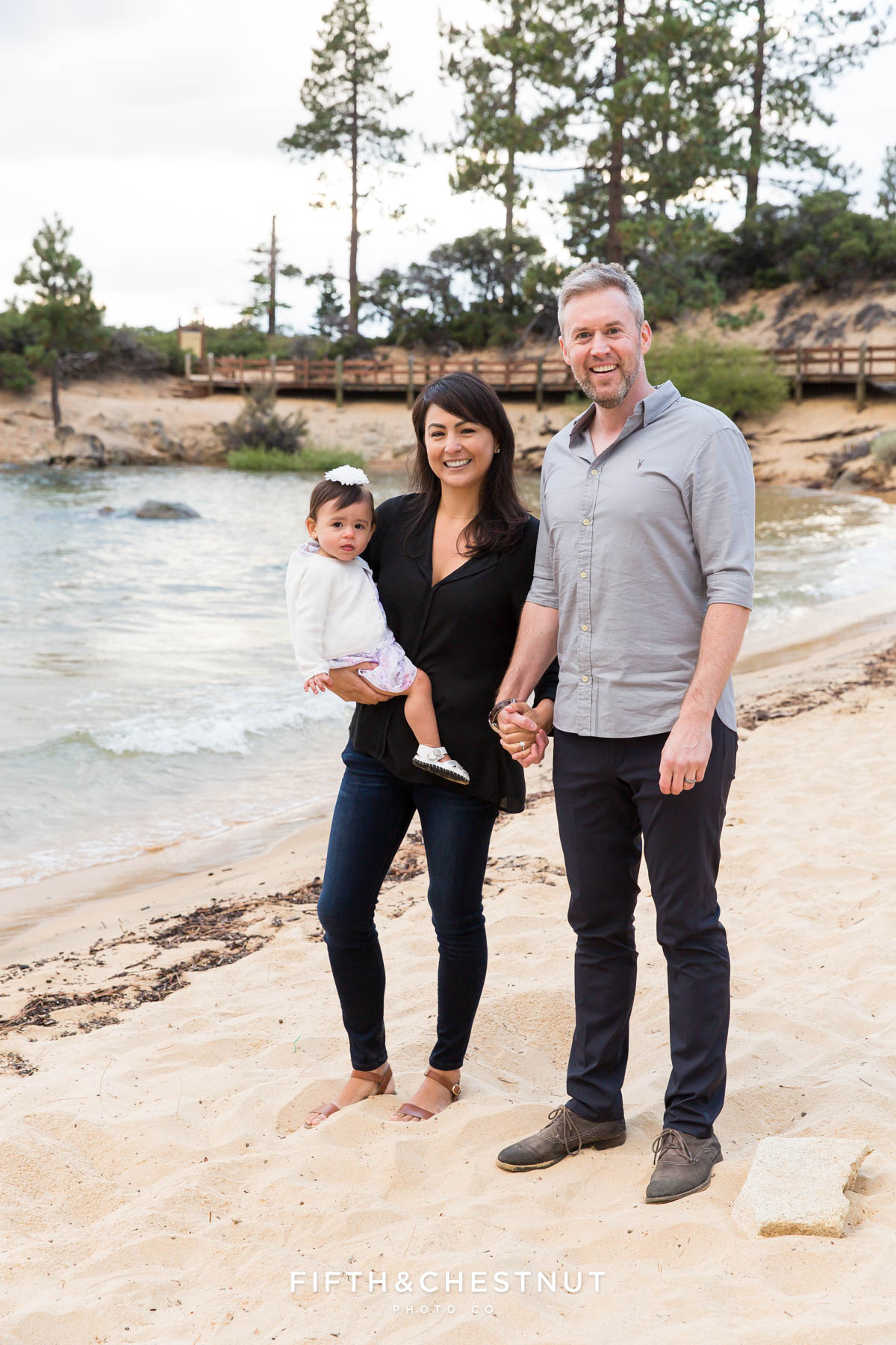 family stands on beach at Sand harbor for their tahoe family portraits