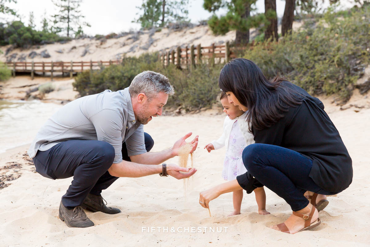 mom and dad play with sand to try and get their toddler interested in posing for her one year portraits at Sand Harbor