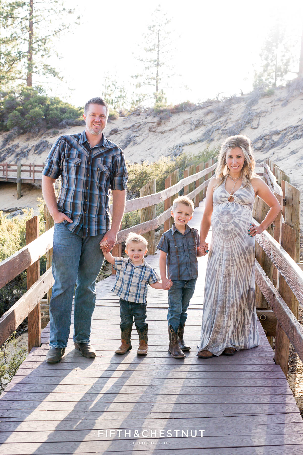 Family holds hands on a wooden path at Sand Harbor for rustic Tahoe Maternity Portraits