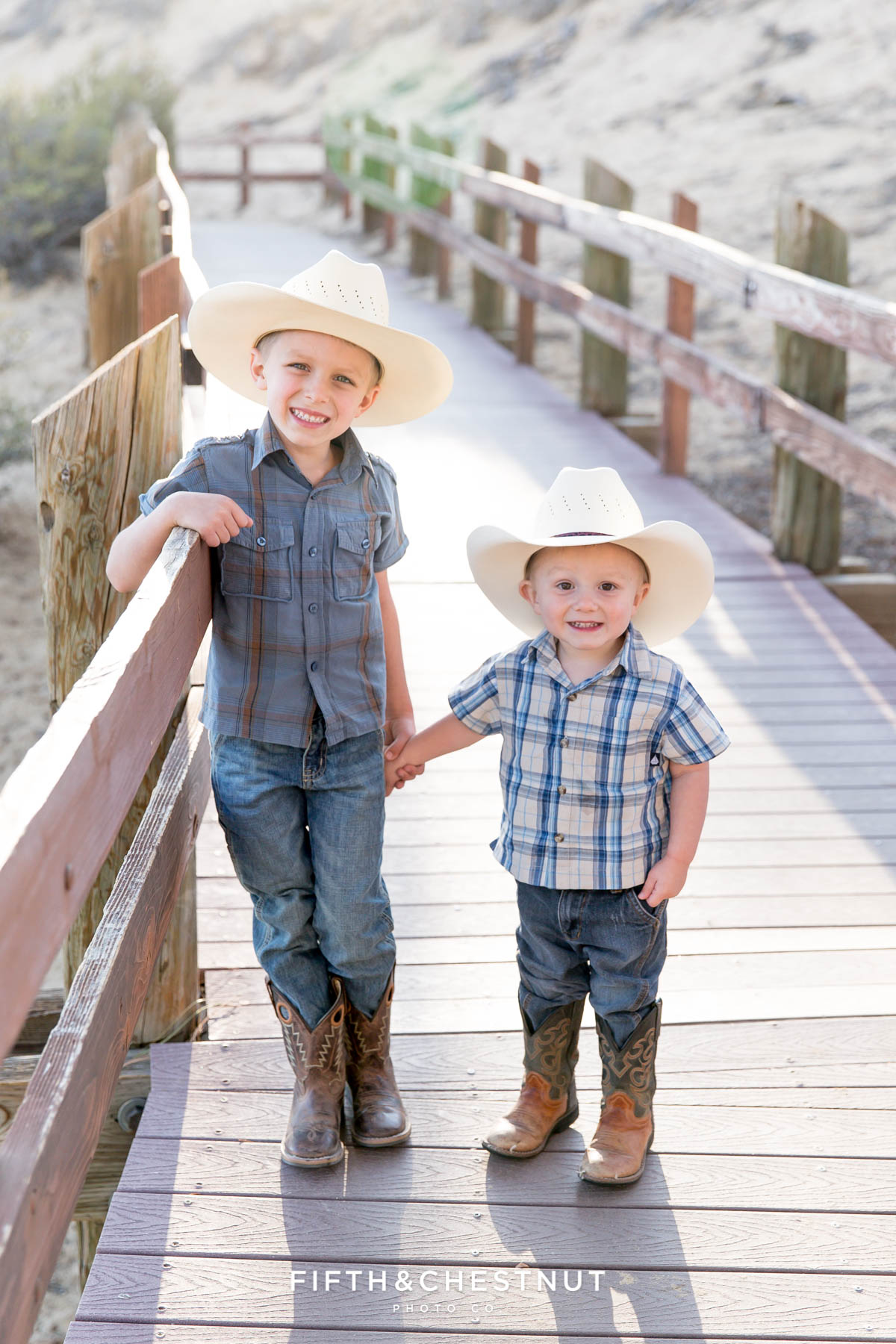 two little boys holding hands on a wooden path wearing plaid shits and cowboy hats