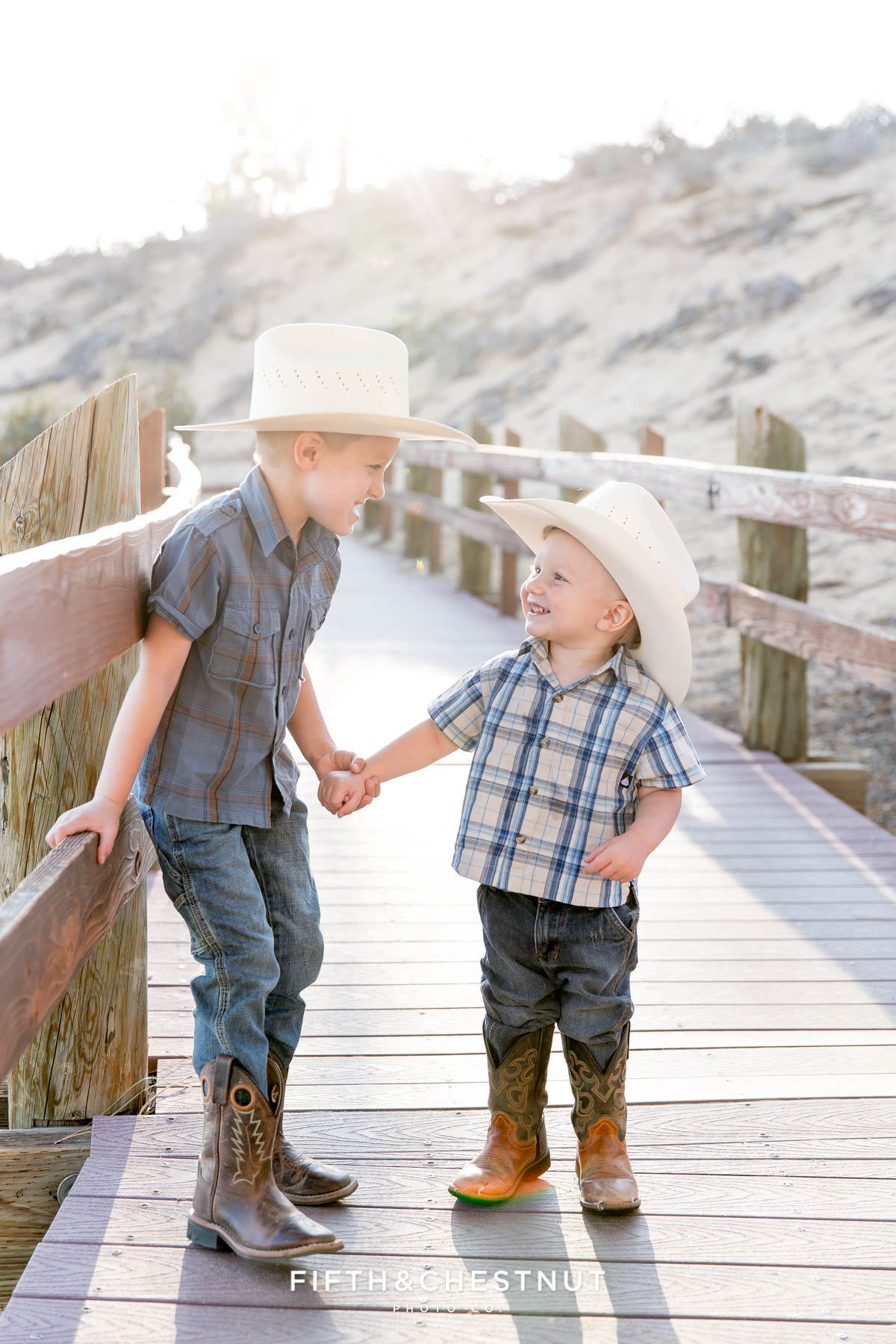 two little boys holding hands on a wooden path wearing plaid shits and cowboy hats giggling at each other