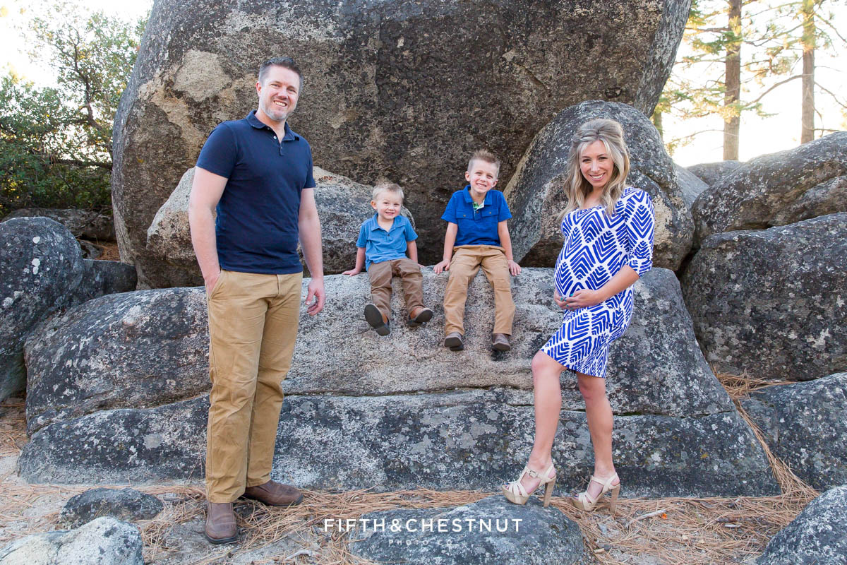 family wearing blue poses in front of big rocks at Sand Harbor for beautiful mama holds her pregnant belly for Tahoe Maternity Portraits