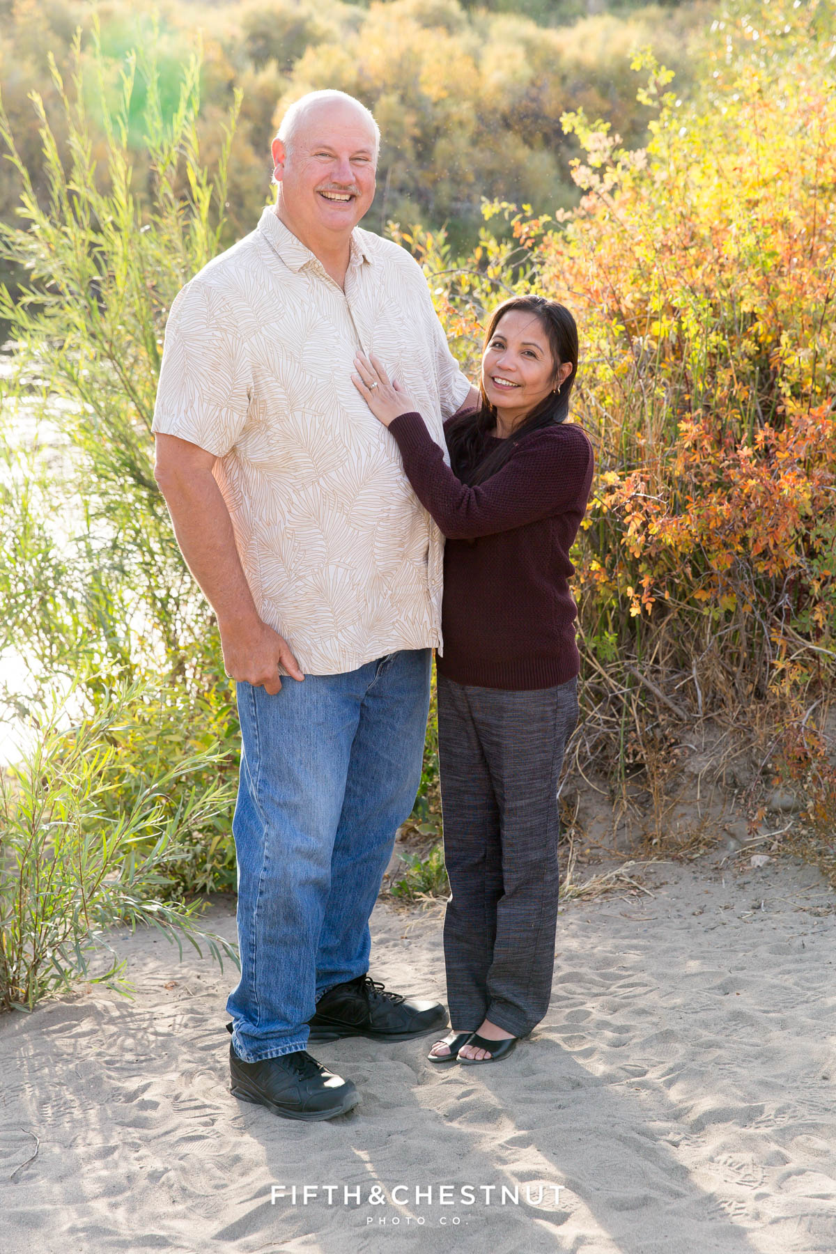 grandparents pose for a photo together in front of the truckee river at mayberry park