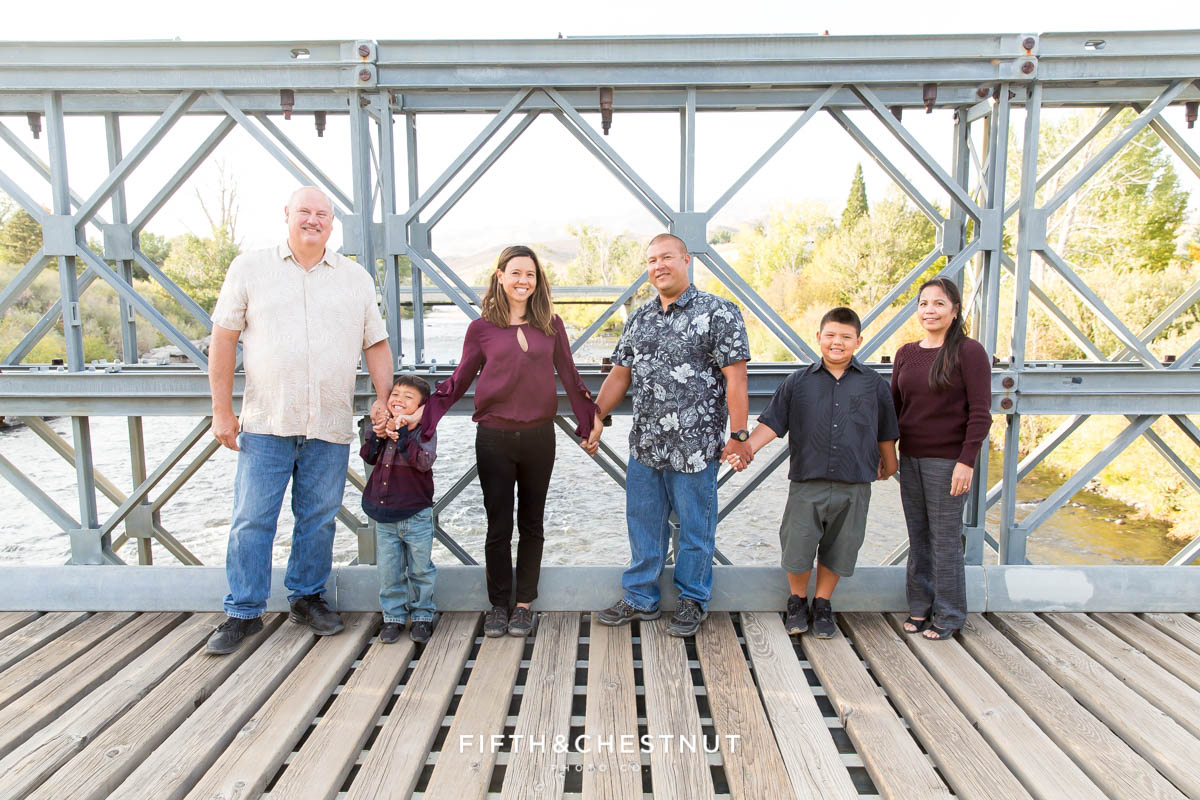 family stands on bridge at mayberry park holding hands in reno, nv