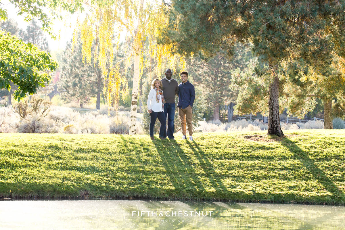 Family of three stands across a pond for fall family portraits at Caughlin Ranch