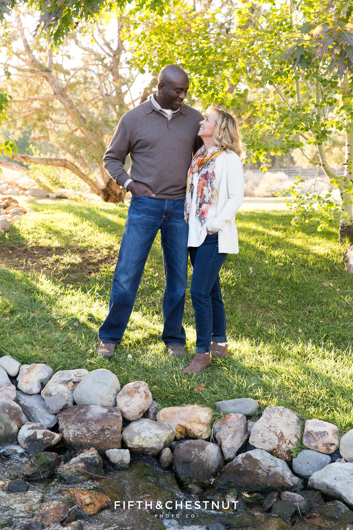 couple laughs with each other for their fall family portraits at Caughlin Ranch