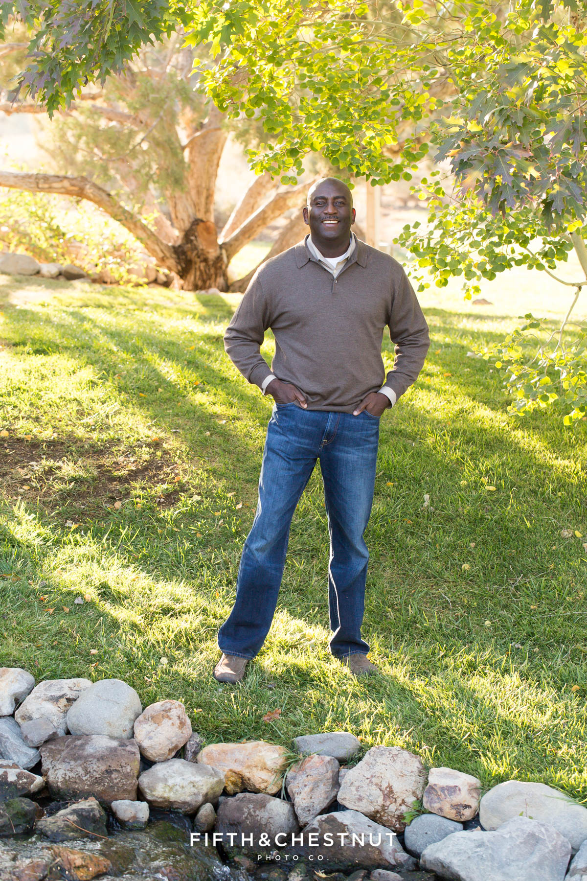 man in brown sweater and jeans poses for his fall family portraits at Caughlin Ranch