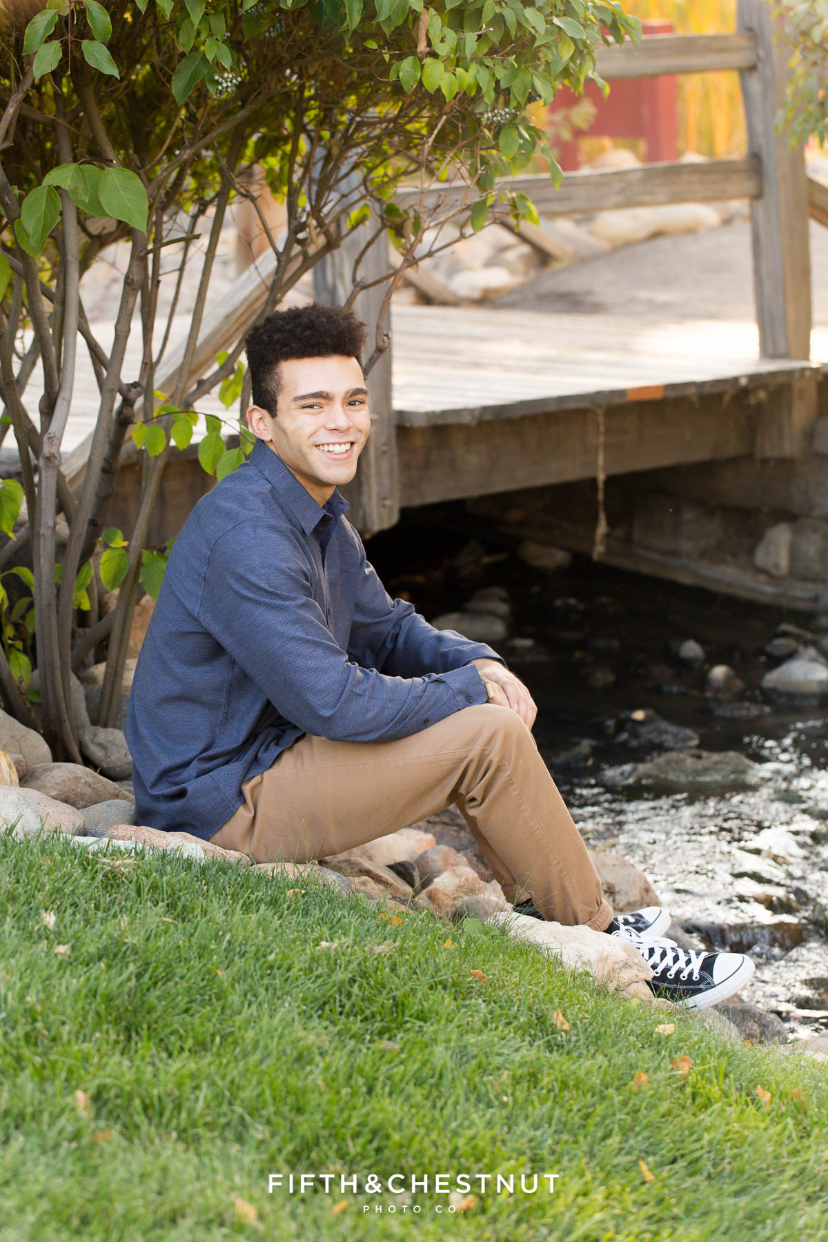 young adult wearing blue and khaki poses near a creek for some fall family portraits in Reno