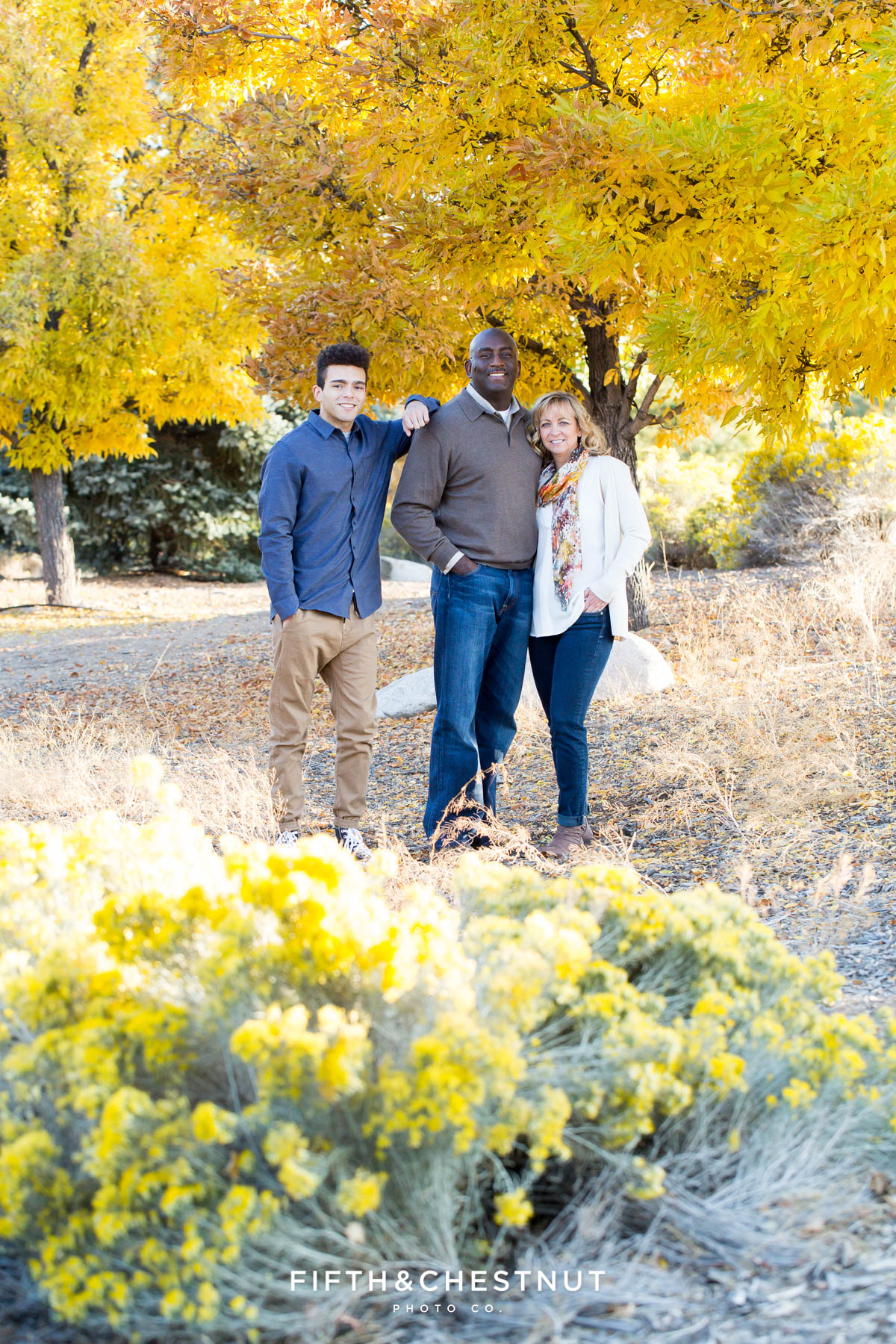 Family of three stands near bright yellow tree for Reno fall family portraits