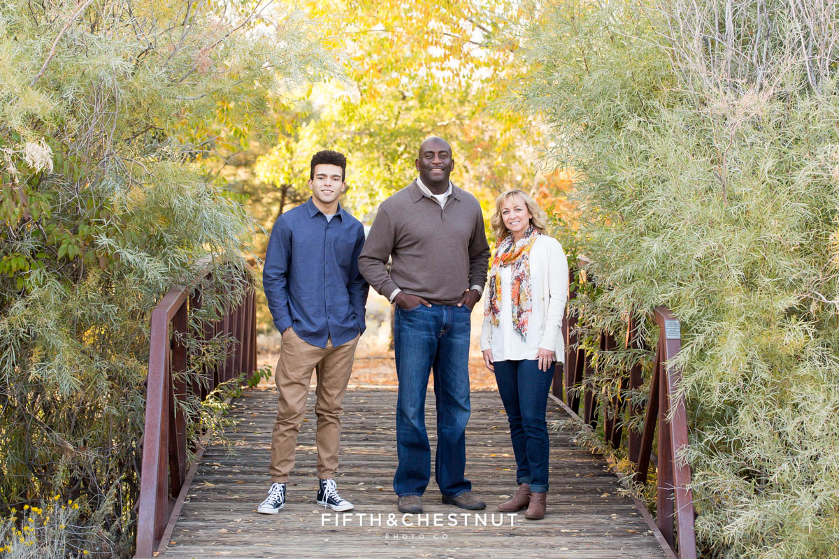 family of three in fall clothing stand on a cool bridge in northwest Reno for Reno fall family portraits