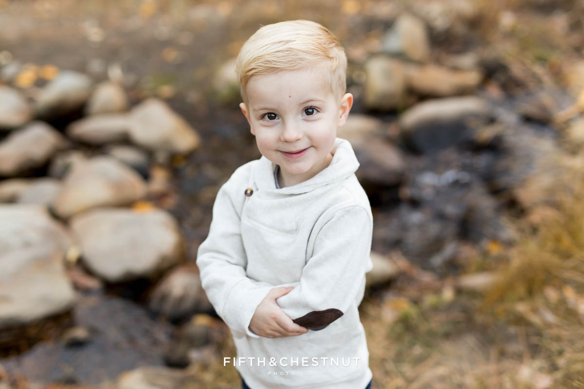 A toddler smiles near a creek during his family's galena creek portraits by Reno Family Photographer
