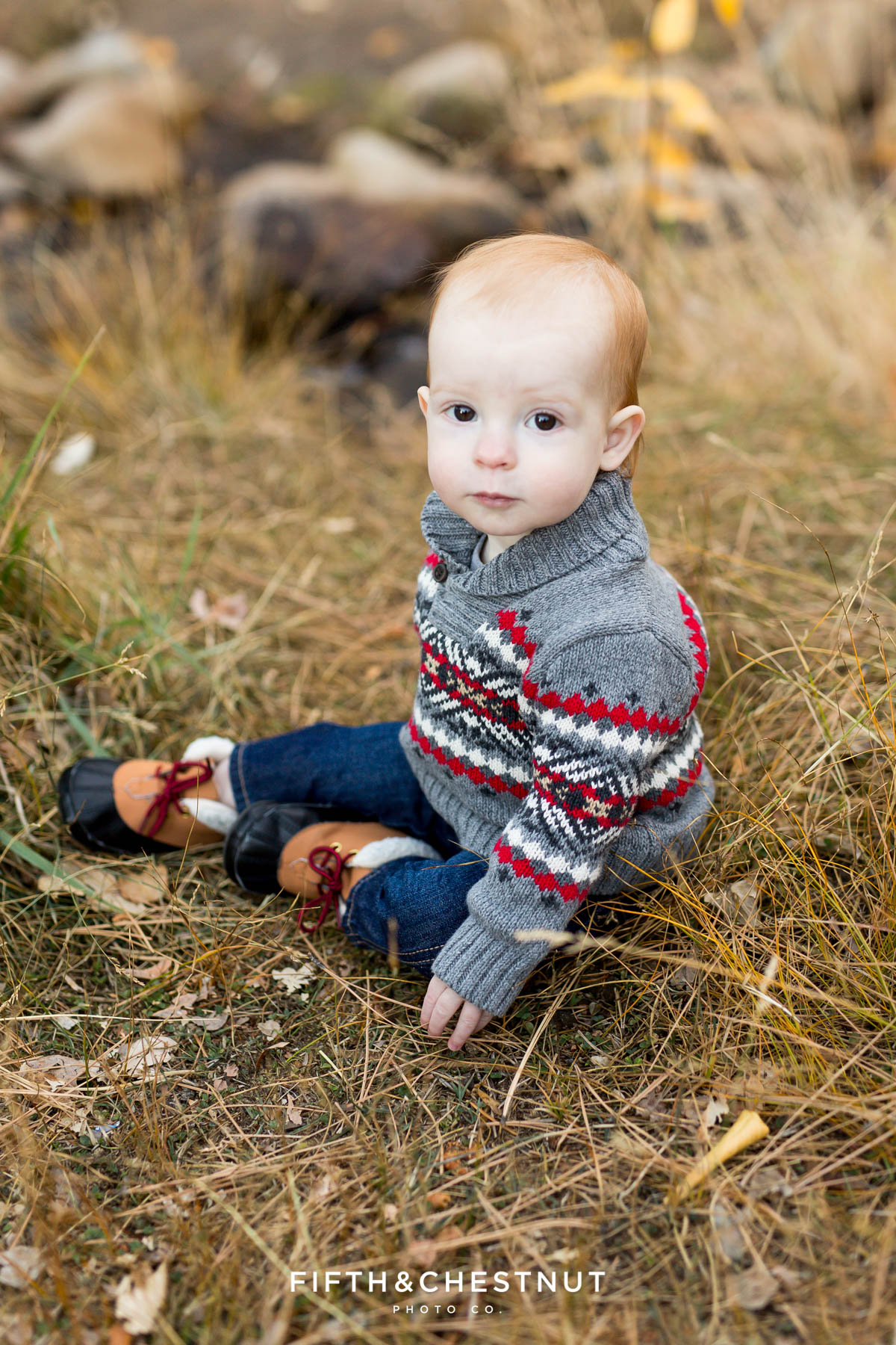 A baby sits in grass for his Fall Galena Creek Portraits
