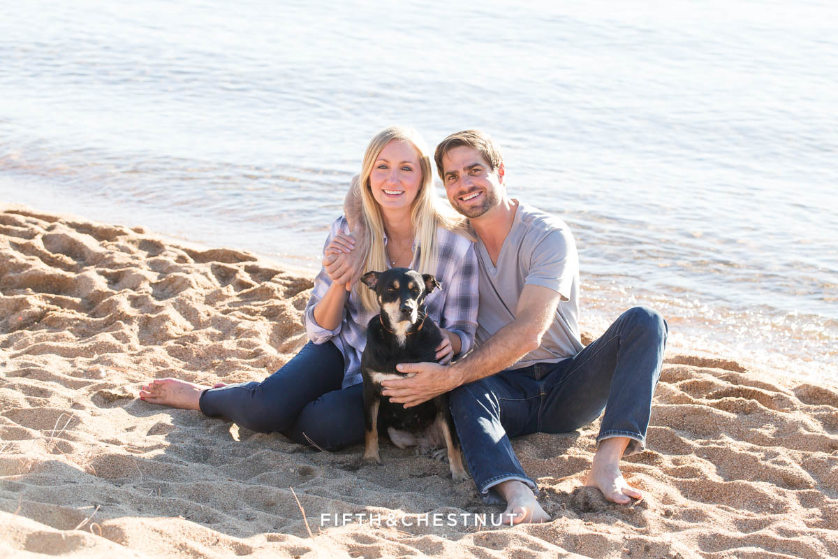 Nevada Beach engagement portrait of engaged couple with their dog on the sand with waves rolling behind them