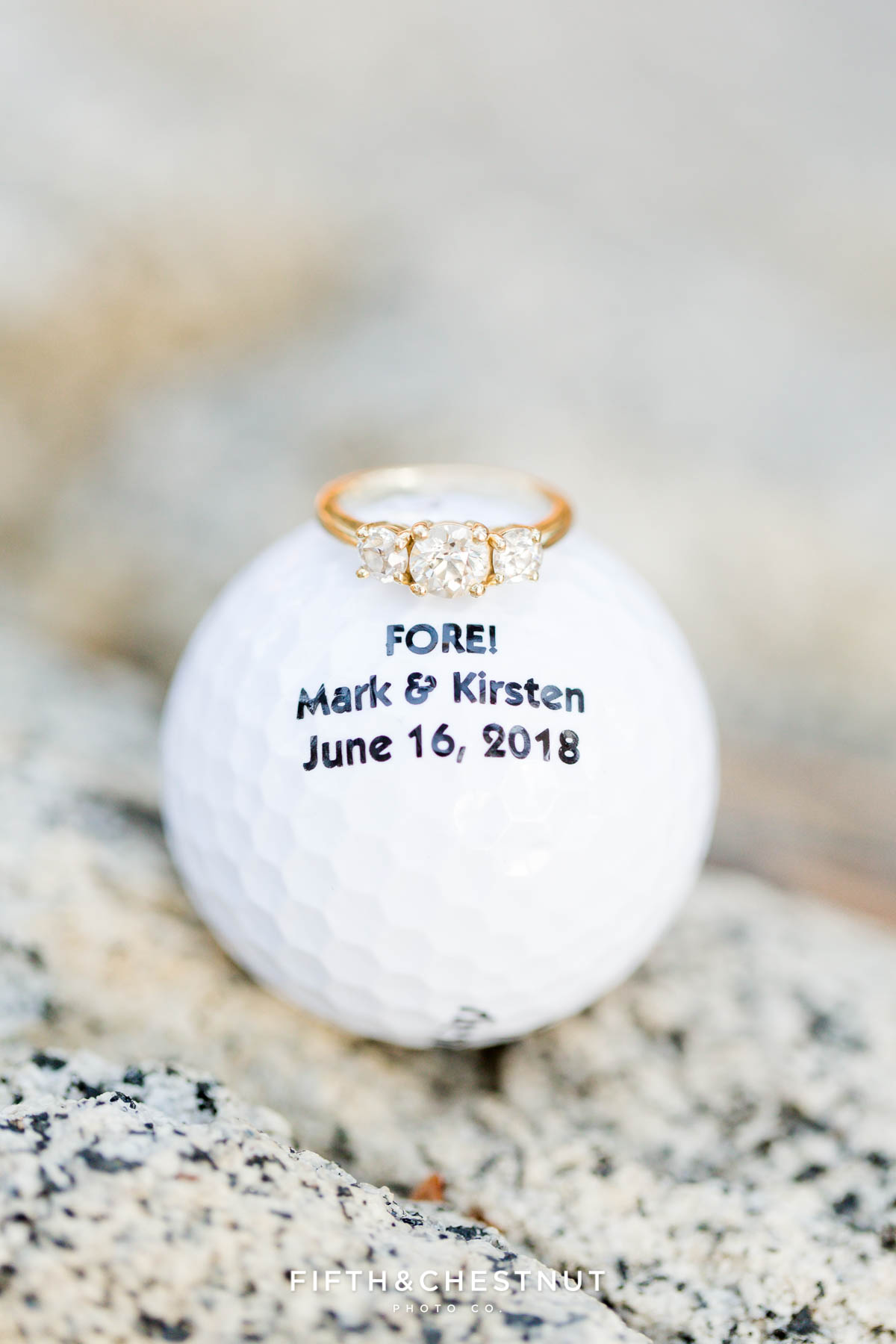 macro photo of engagement ring on a custom engraved golf ball for a Nevada beach engagement by Lake Tahoe Wedding Photographer