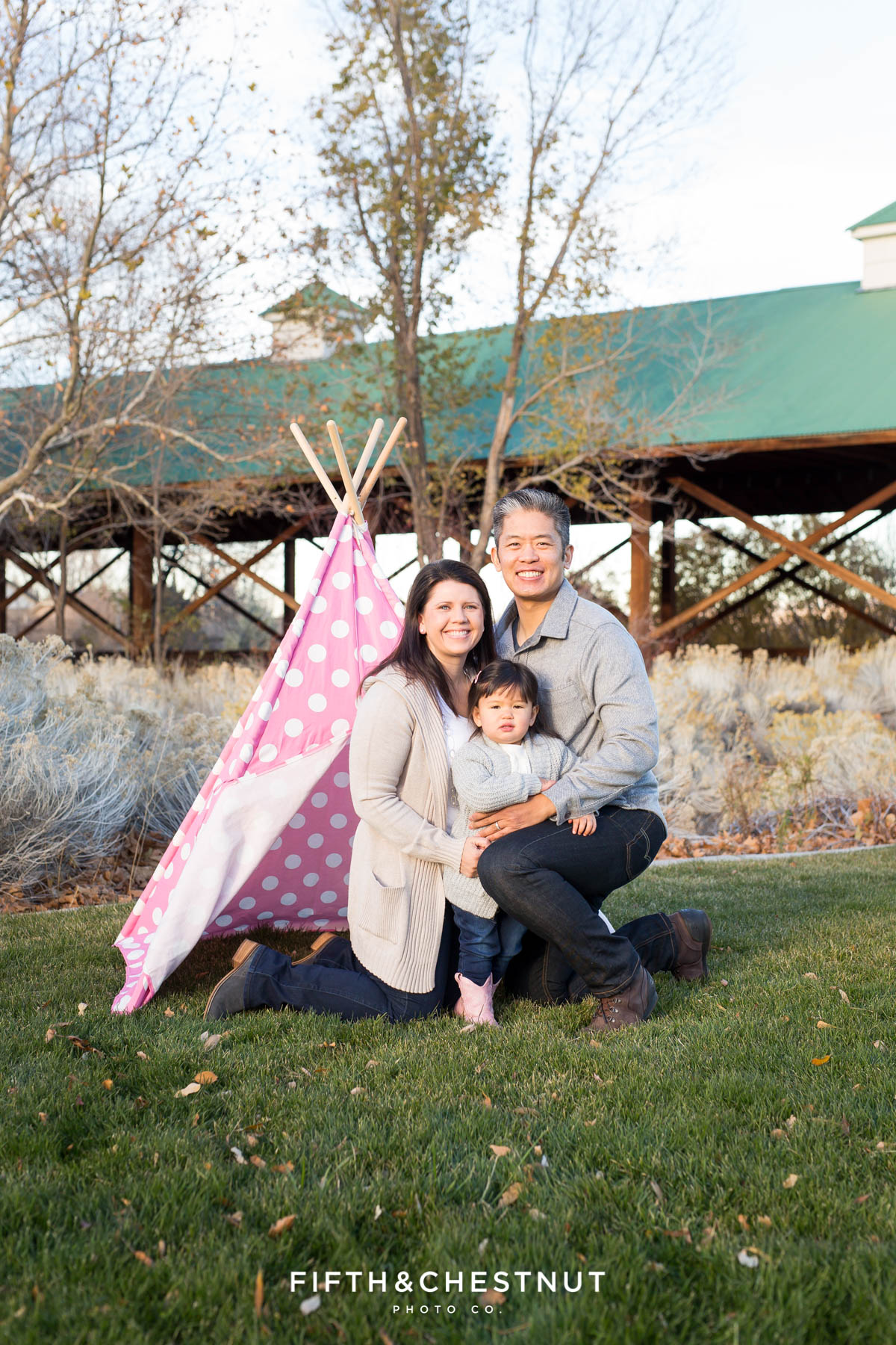 Family of three in front of a pink polka dotted teepee for their Adorable Reno Family Portraits at Bartley Ranch