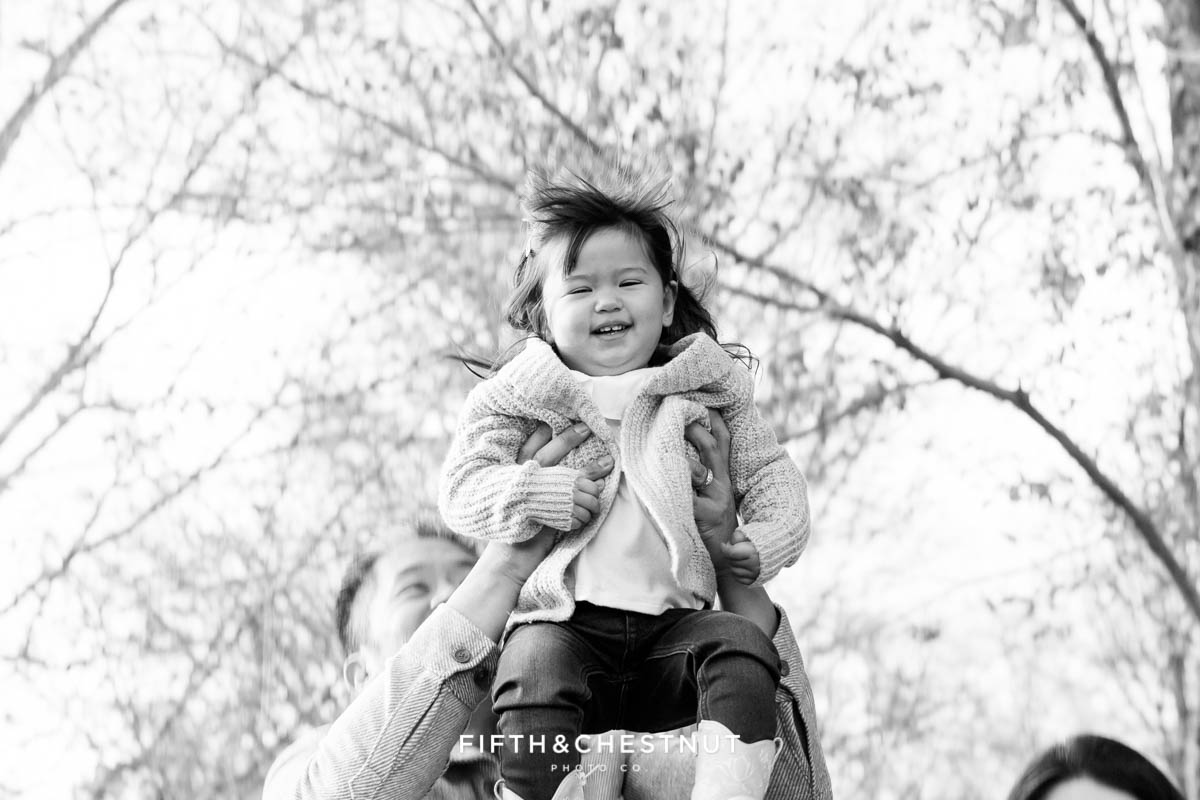 Dad lifts toddler high up into the air for smiles during a Adorable Reno Family Portrait session with Reno Family Photographer